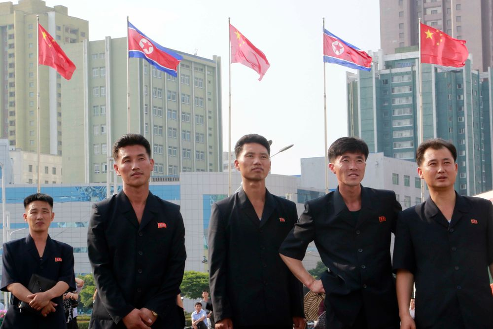 North Koreans watch a large screen reporting Chinese President Xi Jinping's visit in front of the both countries' national flags at Pyongyang Railway Station in Pyongyang, North Korea, Friday, June 21, 2019. Xi offered encouragement for North Korea's focus on economic development in a speech in Pyongyang, turning to a topic Beijing has long pressed with its communist neighbor amid wider concerns over the North's nuclear weapons program. (AP Photo/Jon Chol Jin)
