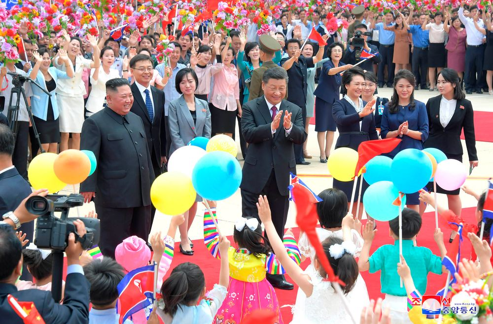 In this Thursday, June 20, 2019, photo provided by the North Korean government, Chinese President Xi Jinping, center, is welcomed by North Koran children at Pyongyang International Airport in Pyongyang, North Korea. North Korean leader Kim Jong Un, left, his wife Ri Sol Ju, second right, and Xi's wife Peng Liyuan, fourth right, also attended a welcoming ceremony. The content of this image is as provided and cannot be independently verified. Korean language watermark on image as provided by source reads: