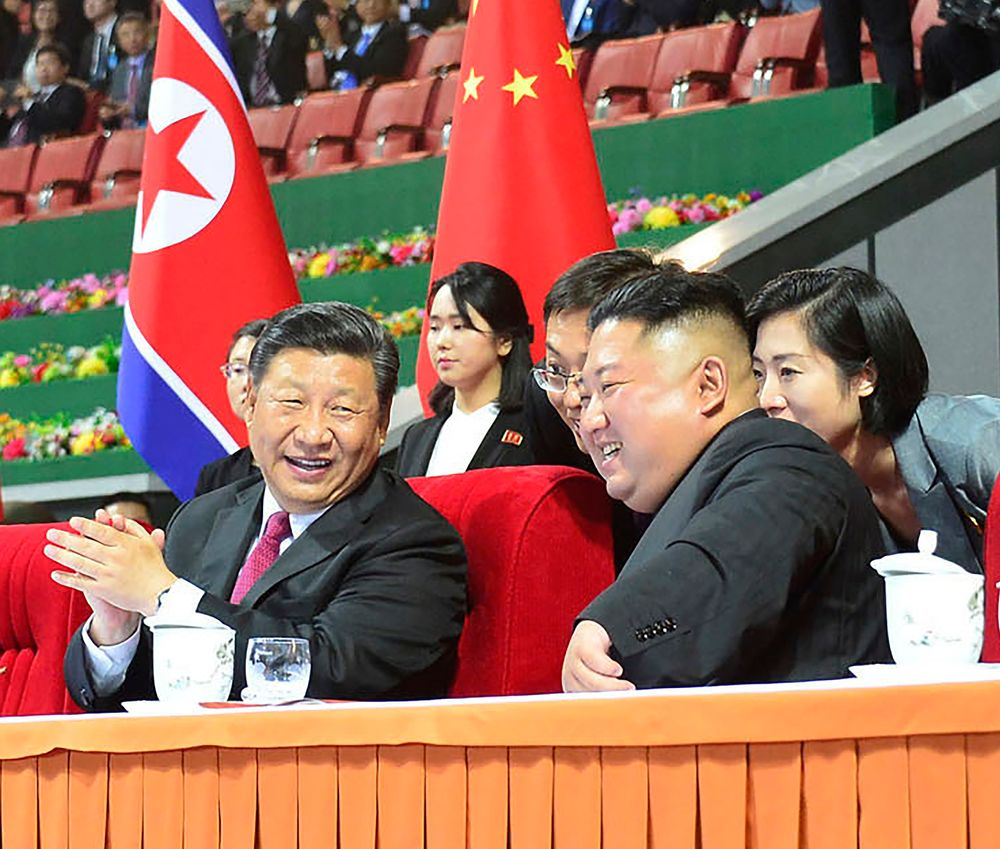 In this Thursday, June 20, 2019, photo provided by the North Korean government, North Korean leader Kim Jong Un, right, and Chinese President Xi Jinping, left, watch a mass gymnastic performance at the May Day Stadium in Pyongyang, North Korea. The content of this image is as provided and cannot be independently verified. (Korean Central News Agency/Korea News Service via AP)