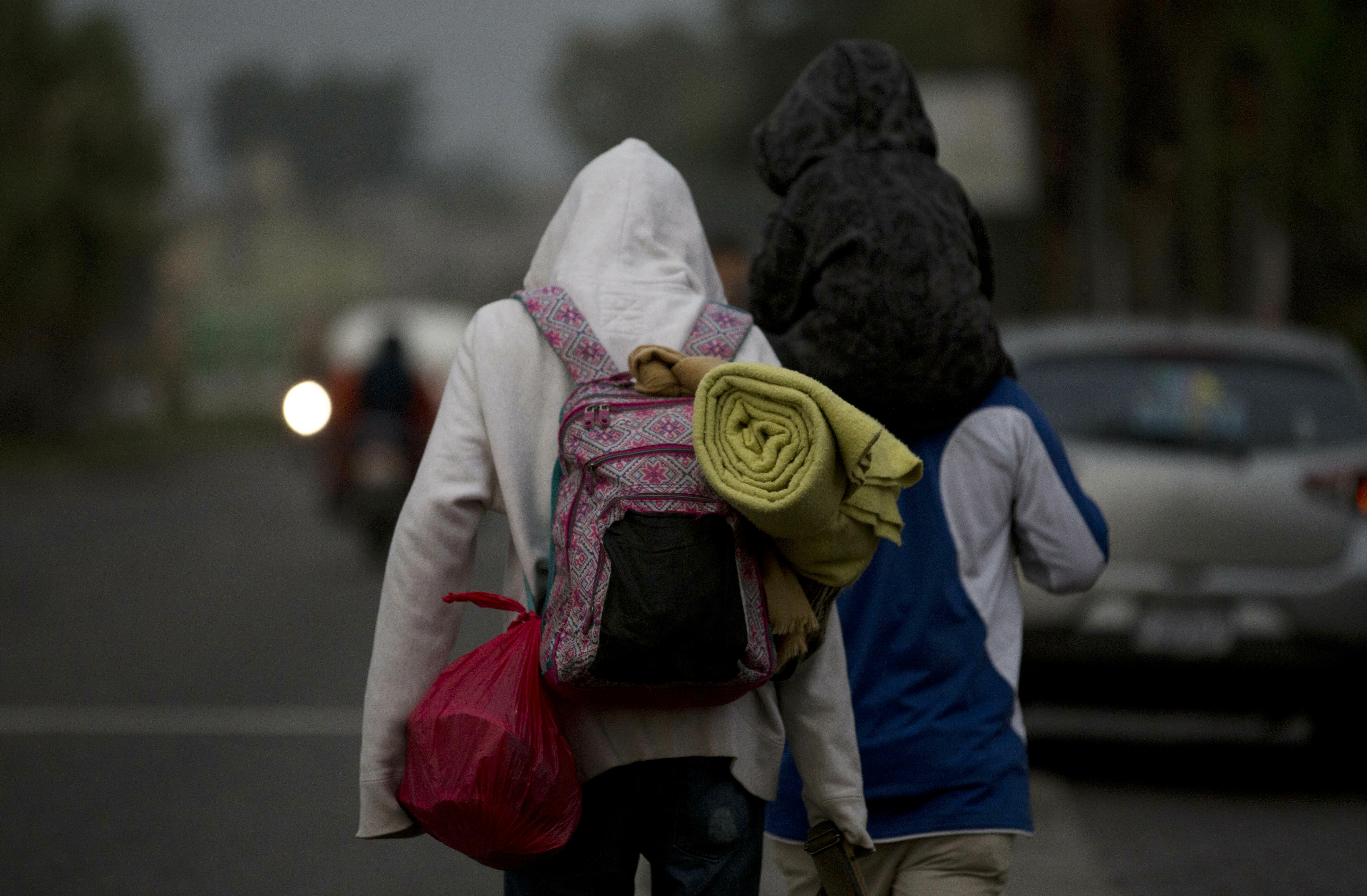 Honduran migrants carry their belongings on their backs as they walk at dawn along the roadside through Esquipulas, Guatemala, as they make their way toward the U.S. border, Wednesday, Jan. 16, 2019. The latest caravan of Honduran migrants hoping to reach the U.S. has crossed into Guatemala. (AP Photo/Moises Castillo)
