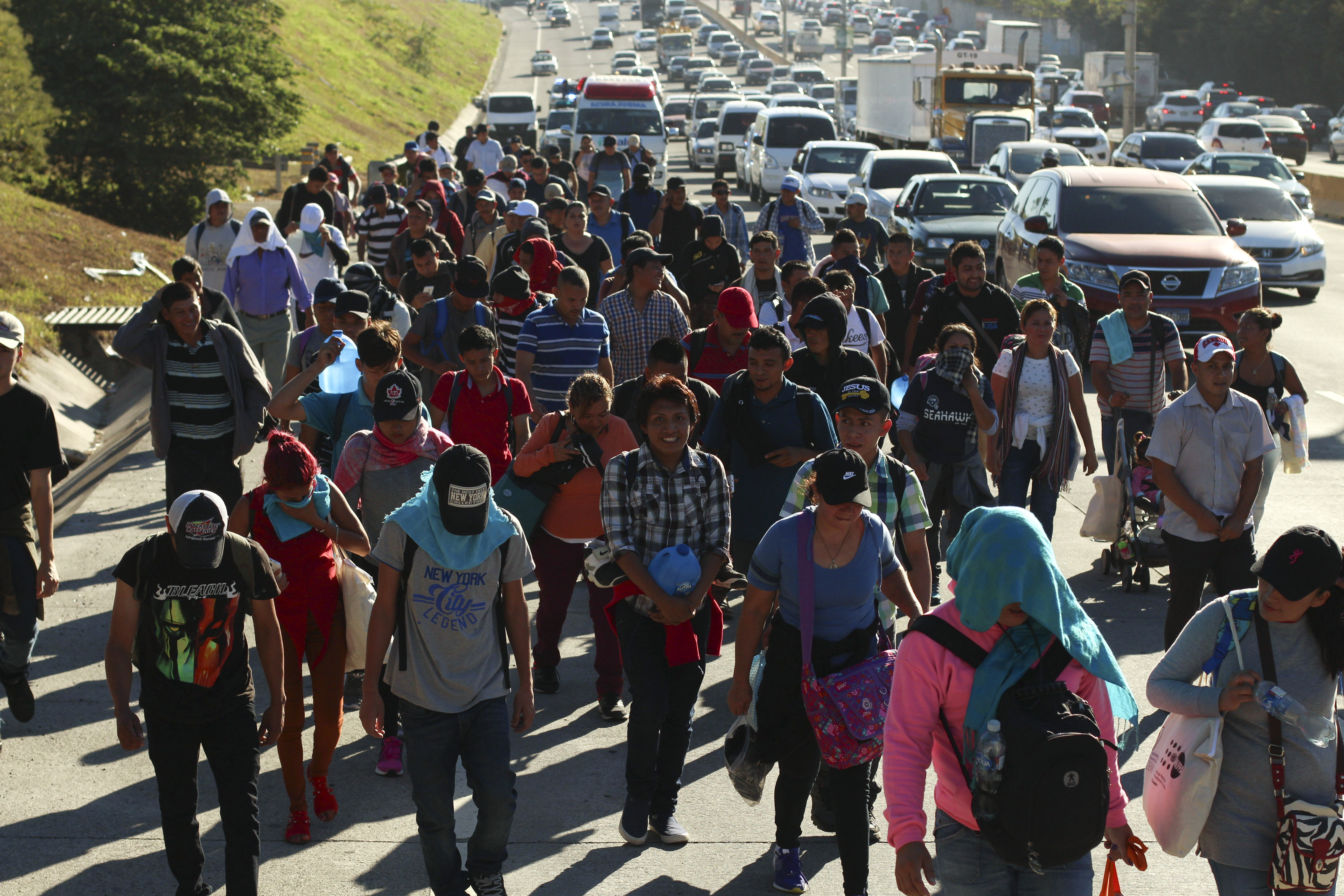 Migrants traveling in a group begin their journey toward the U.S. border as they walk along a highway in San Salvador, El Salvador, early Wednesday, Jan. 16, 2019. Migrants fleeing Central America's Northern Triangle region comprising Honduras, El Salvador and Guatemala routinely cite poverty and rampant gang violence as their motivation for leaving. (AP Photo/Salvador Melendez)