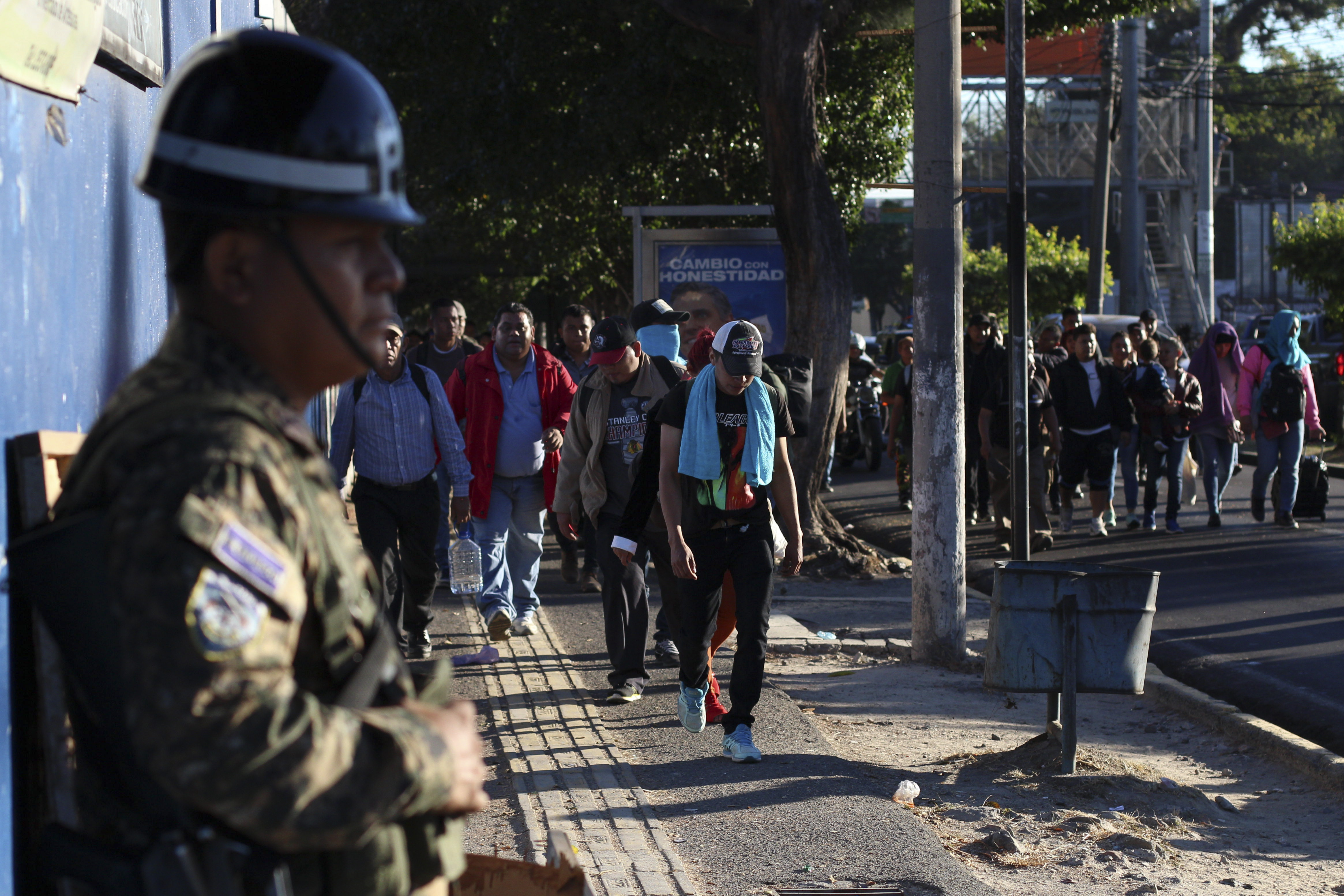 Police stand by as locals begin their journey north toward the U.S. border, during a migrant caravan passing through the capital of San Salvador, El Salvador, early Wednesday, Jan. 16, 2019. Migrants fleeing Central America's Northern Triangle region comprising Honduras, El Salvador and Guatemala routinely cite poverty and rampant gang violence as their motivation for leaving. (AP Photo/Salvador Melendez)