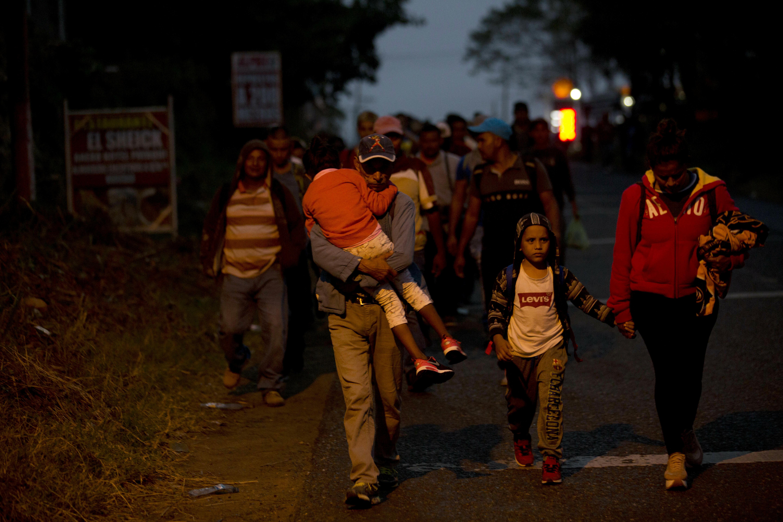 Honduran migrants walk at dawn along the roadside through Esquipulas, Guatemala, as they make their way toward the U.S. border, Wednesday, Jan. 16, 2019. The latest caravan of Honduran migrants hoping to reach the U.S. has crossed into Guatemala. (AP Photo/Moises Castillo)