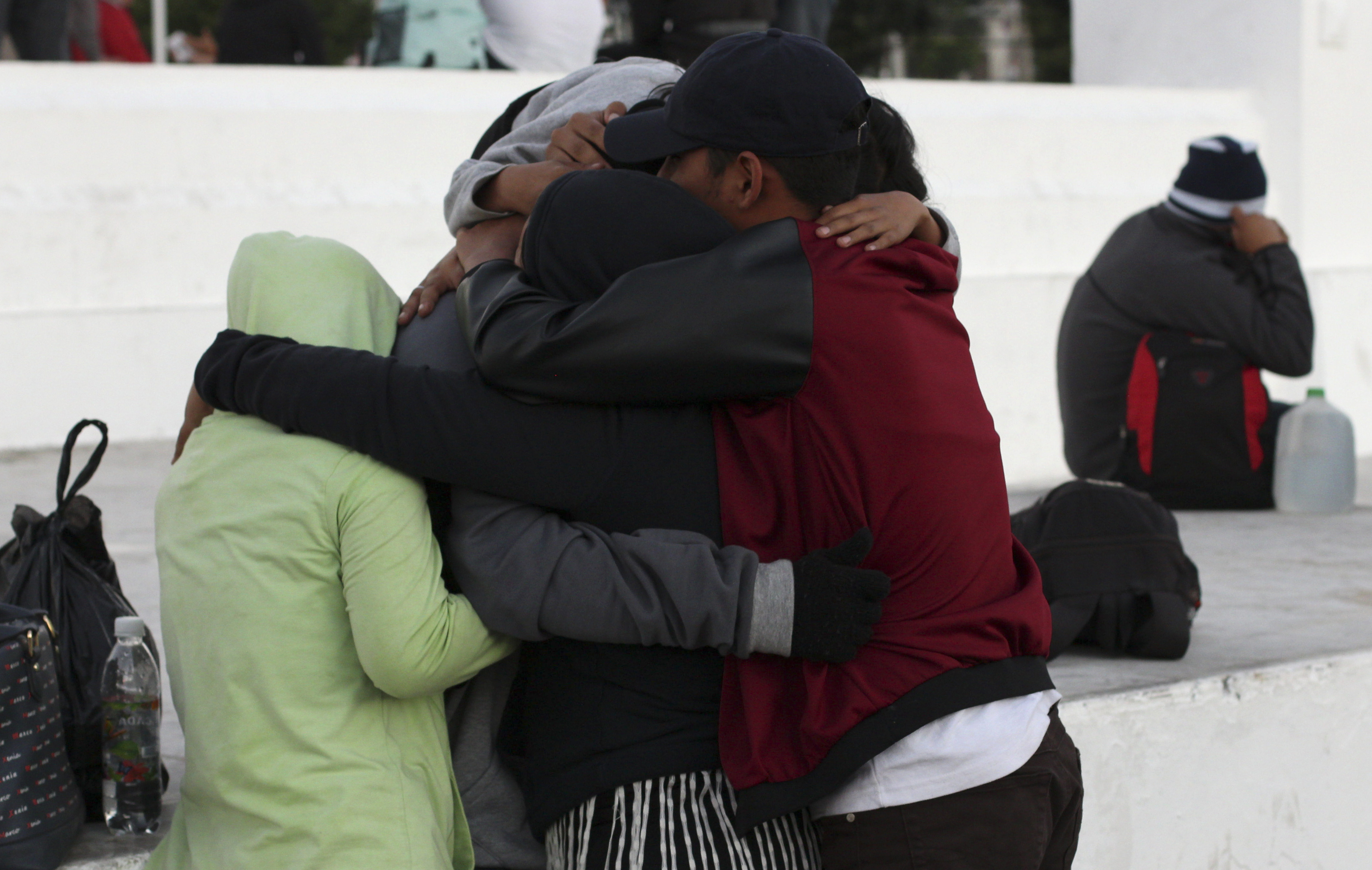 A man hugs his family before setting off toward the U.S. border with a migrant caravan from San Salvador, El Salvador, Wednesday, Jan. 16, 2019. Migrants fleeing Central America's Northern Triangle region comprising Honduras, El Salvador and Guatemala routinely cite poverty and rampant gang violence as their motivation for leaving. (AP Photo/Salvador Melendez)