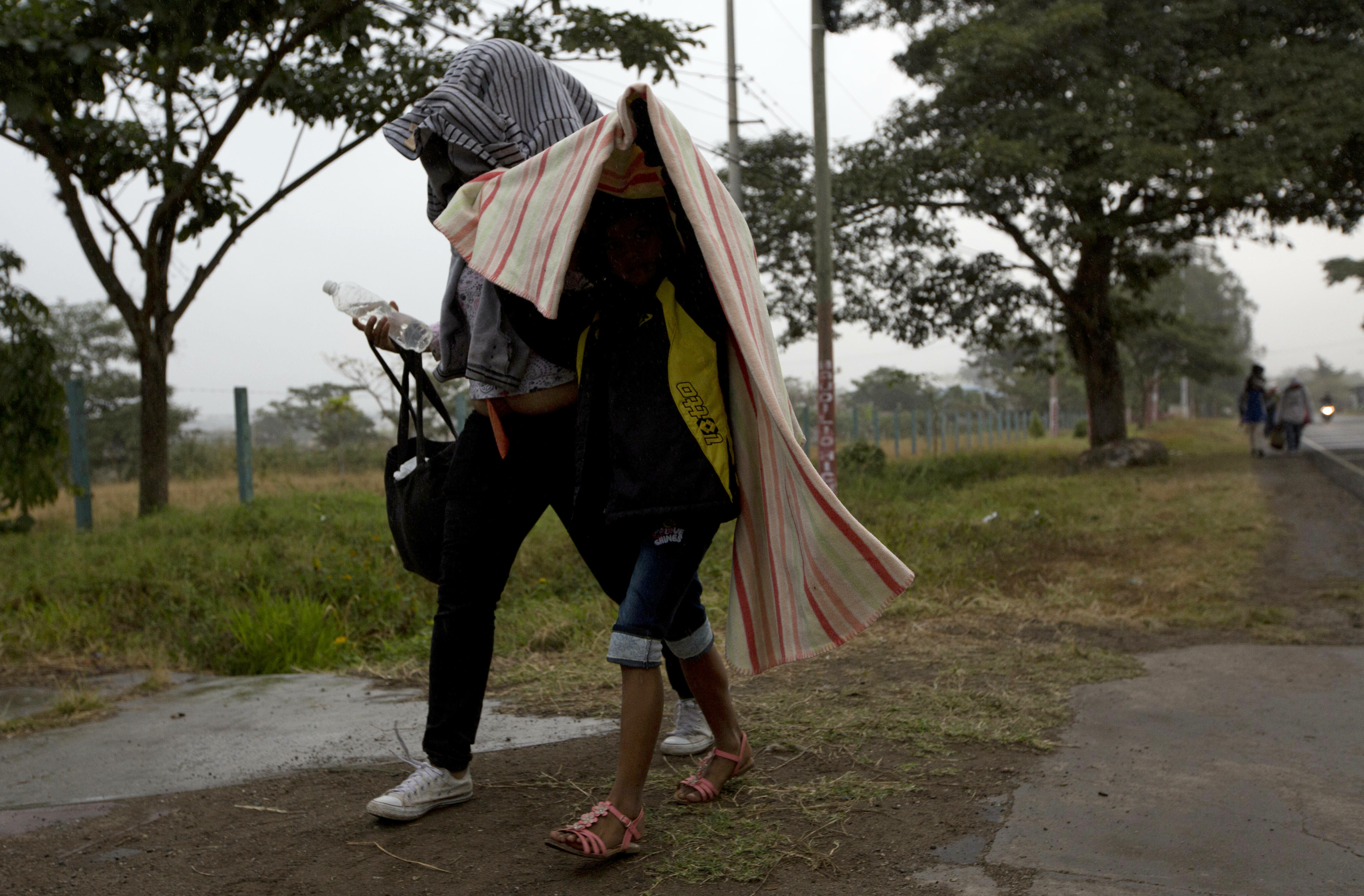Honduran migrants shield themselves from a light rain as they walk north along the roadside through Esquipulas, Guatemala, early Wednesday, Jan. 16, 2019. The latest caravan of Honduran migrants hoping to reach the U.S. has crossed into Guatemala. (AP Photo/Moises Castillo)