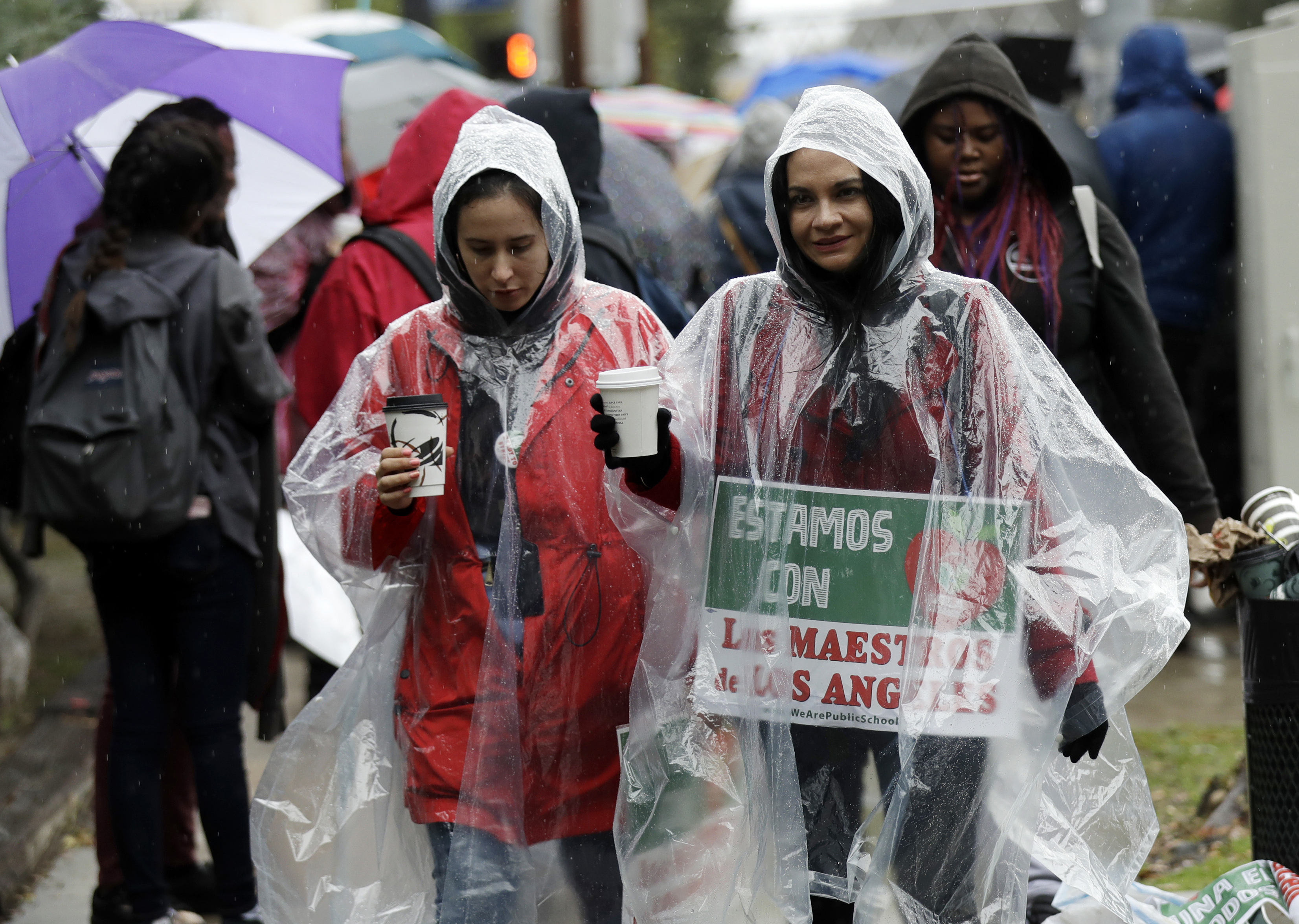 Spanish teachers Natalie Ardagna, right, and Jenny Padilla cover themselves from the rain as they protest outside of North Hollywood High School Tuesday, Jan. 15, 2019, in Los Angeles. Teachers in the huge Los Angeles Unified School District walked picket lines again Tuesday as administrators urged them to return to classrooms and for their union to return to the bargaining table. (AP Photo/Marcio Jose Sanchez)