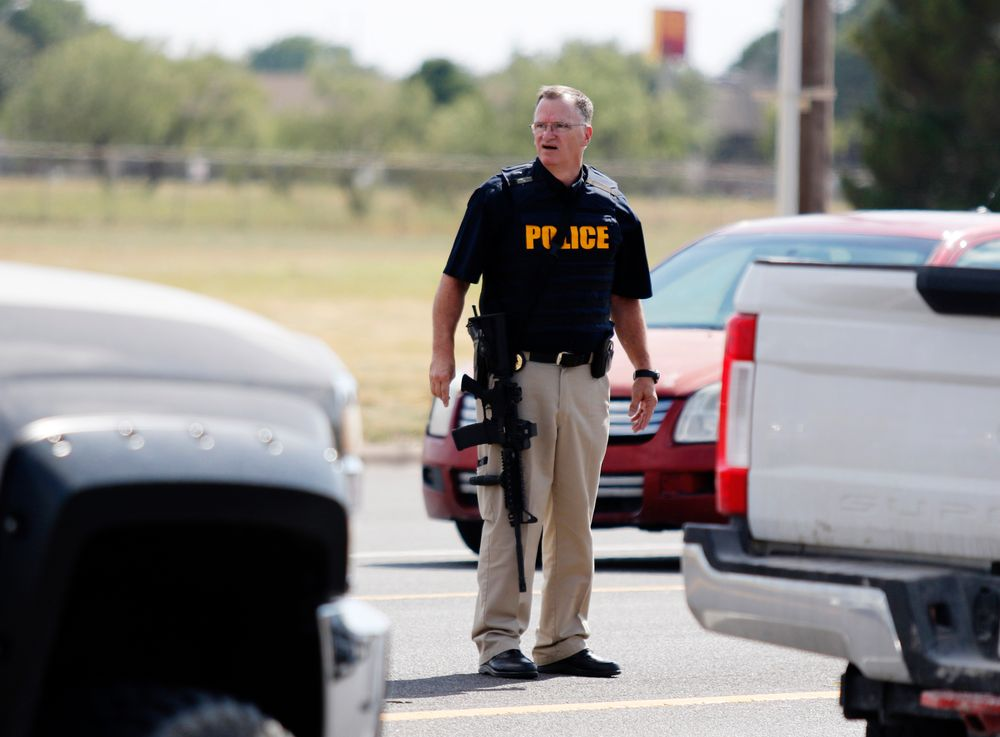 A law enforcement officer stands in the middle of the 5100 block of E. 42nd Street in Odessa, Texas, Saturday, Aug. 31, 2019, following a shooting at random in the area of Odessa and Midland. Several people were dead after a gunman who hijacked a postal service vehicle in West Texas shot more than 20 people, authorities said Saturday. The gunman was killed and a few law enforcement officers were among the injured. (Mark Rogers/Odessa American via AP)