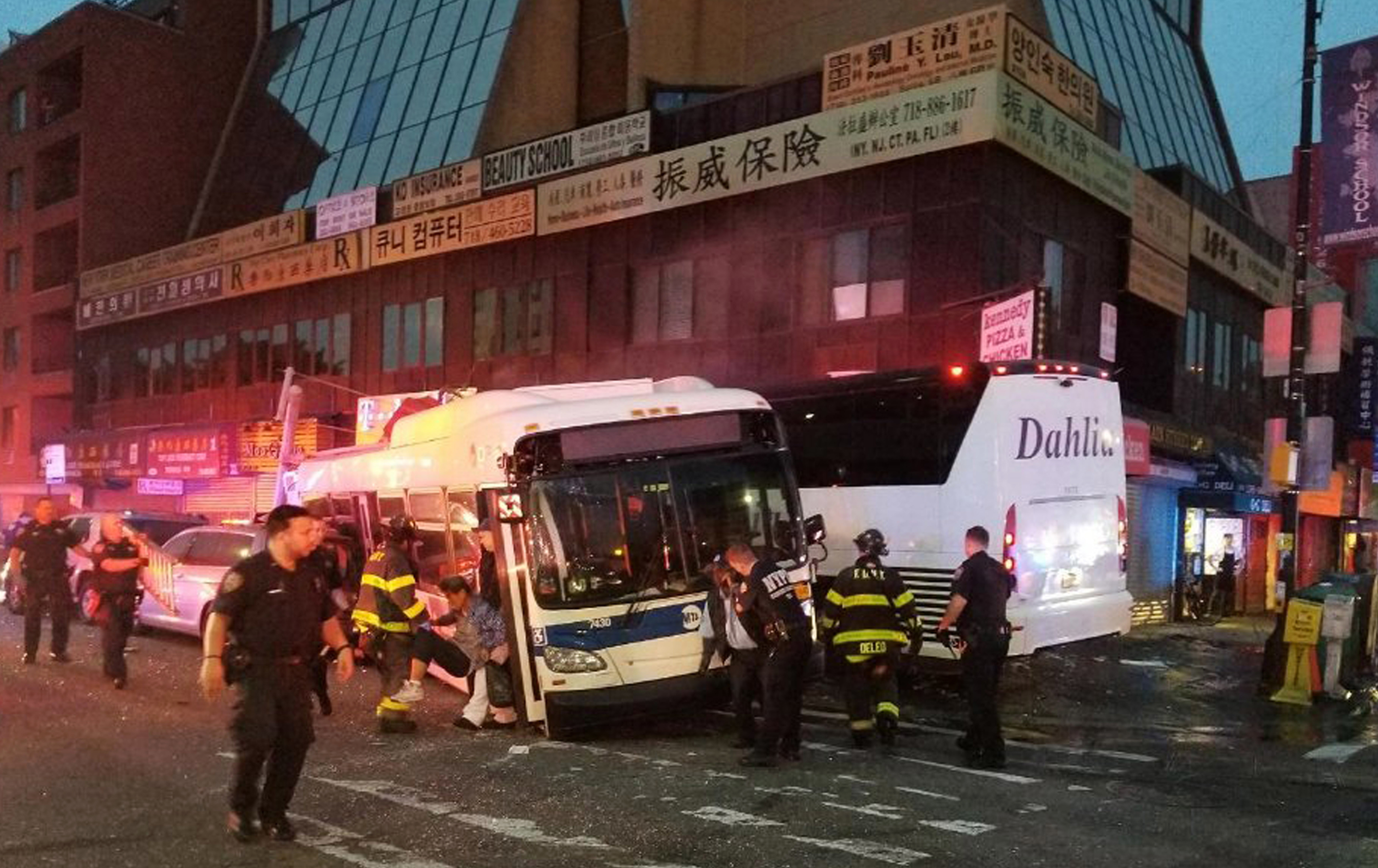 FILE - In this Monday, Sept. 18, 2017 photo provided by the NYPD's 109th Precinct, officers respond to a collision involving two buses on Main Street in the Queens borough of New York.  Federal safety investigators say a freak accident involving a dropped thermos may have caused a bus crash that killed three people in New York City. The National Transportation Safety Board released its report Thursday, Feb. 21, 2019.  The incident occurred when a charter bus blew threw a Queens intersection at 60 mph, slammed into a city bus, barreled across a sidewalk and hit a building. The charter bus driver, a city bus passenger and a pedestrian were killed.  (NYPD's 109th Precinct via AP, File)