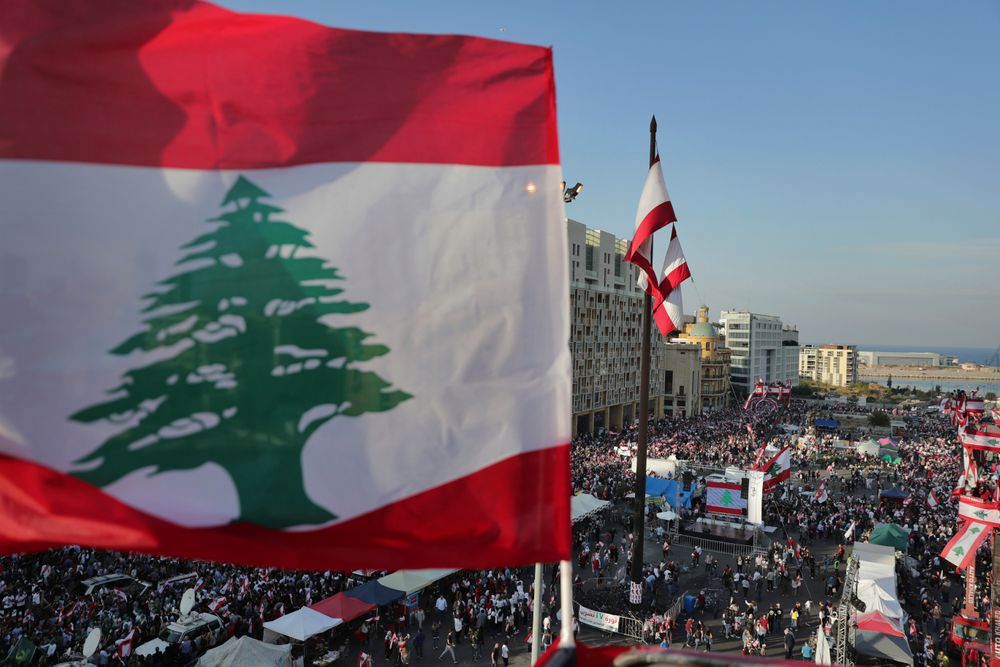 Anti-government protesters gather during separate civil parade at the Martyr square, in downtown Beirut, Lebanon, Friday, Nov. 22, 2019. Protesters gathered for their own alternative independence celebrations, converging by early afternoon on Martyrs' square in central Beirut, which used to be the traditional location for the official parade. Protesters have occupied the area, closing it off to traffic since mid-October. (AP Photo/Hassan Ammar)