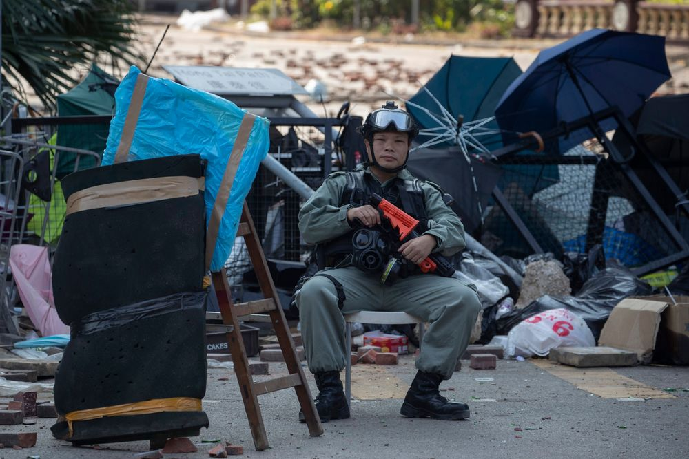 A police officer watches the Polytechnic University entrance in Hong Kong on Wednesday, Nov. 20, 2019. A small group of protesters refused to leave Hong Kong Polytechnic University, the remnants of hundreds who took over the campus for several days. They won't leave because they would face arrest. Police have set up a cordon around the area to prevent anyone from escaping. (AP Photo/Ng Han Guan)