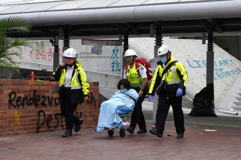 Medical workers escort a protester from Hong Kong Polytechnic University in Hong Kong, Wednesday, Nov. 20, 2019. A small band of anti-government protesters, their numbers diminished by surrenders and failed escape attempts, remained holed up at a Hong Kong university early Wednesday as they braced for the endgame in a police siege of the campus. (AP Photo/Vincent Yu)