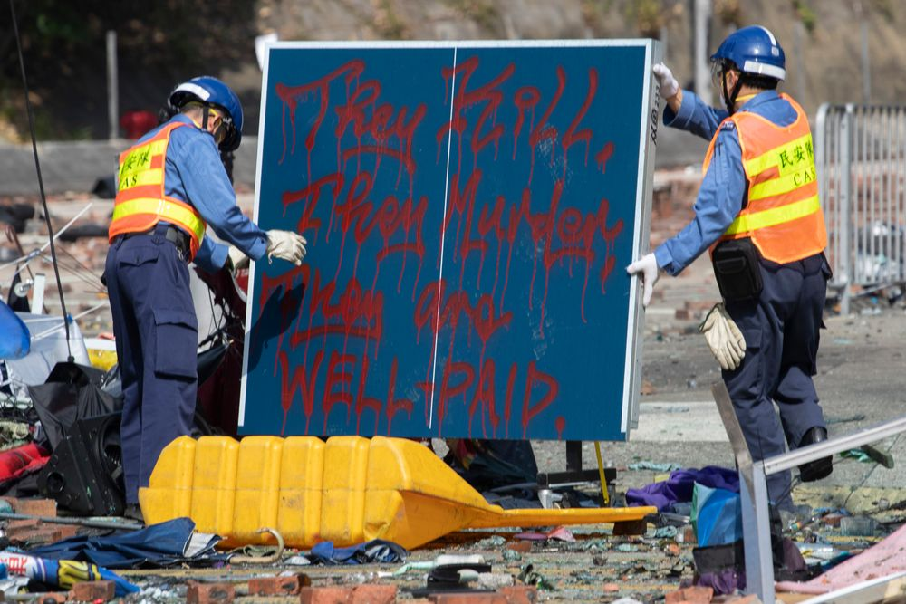 Workers remove a board with the words referring to the police force