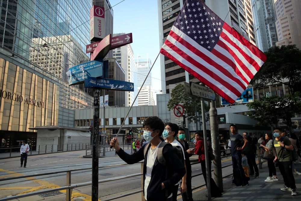 A protester holds an American flag during a demonstration in the financial district in Hong Kong, Wednesday, Nov. 20, 2019. Hong Kong schools reopened Wednesday after a six-day shutdown but students and commuters faced transit disruptions as the last protesters remained holed up on a university campus. (AP Photo/Kin Cheung)