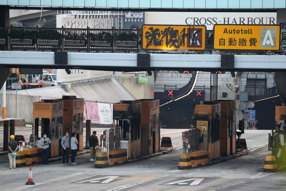 Workers inspect the damage from protesters on the toll booths of the Cross-Harbor Tunnel near the Polytechnic University in Hong Kong on Wednesday, Nov. 20, 2019. A small group of protesters refused to leave Hong Kong Polytechnic University, the remnants of hundreds who took over the campus for several days. They won't leave because they would face arrest. Police have set up a cordon around the area to prevent anyone from escaping. (AP Photo/Ng Han Guan)