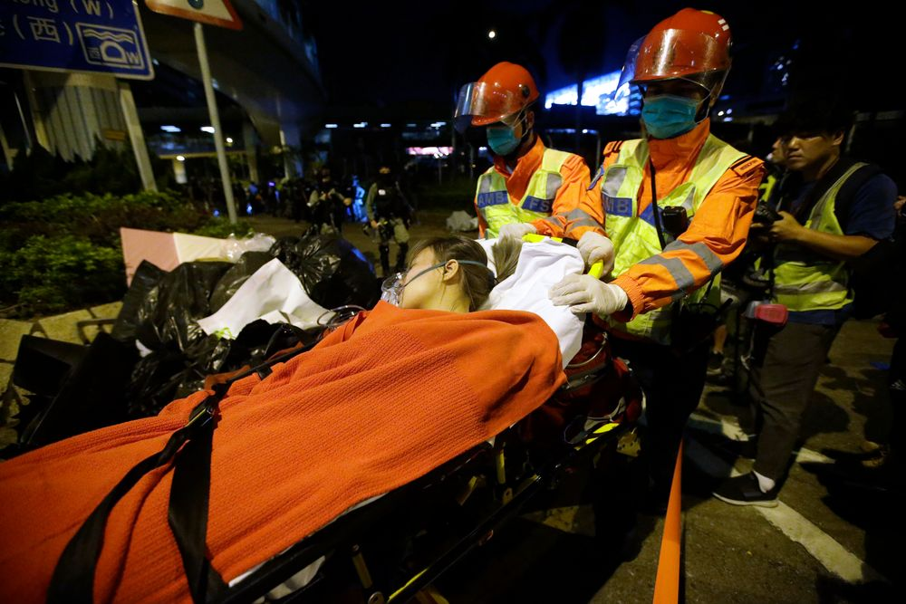Medical workers transport an injured protester on a stretcher near Hong Kong Polytechnic University in Hong Kong, Tuesday, Nov. 19, 2019. A small band of anti-government protesters, their numbers diminished by surrenders and failed escape attempts, remained holed up at a Hong Kong university early Wednesday as they braced for the endgame in a police siege of the campus. (AP Photo/Achmad Ibrahim)