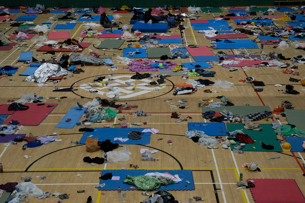 Protesters rest in a gymnasium on the campus of the Polytechnic University in Hong Kong on Wednesday, Nov. 20, 2019. A small group of protesters refused to leave Hong Kong Polytechnic University, the remnants of hundreds who took over the campus for several days. They won't leave because they would face arrest. Police have set up a cordon around the area to prevent anyone from escaping. (AP Photo/Ng Han Guan)