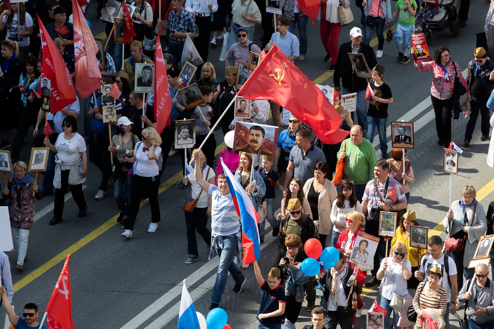 People carry portraits of relatives who fought in World War II, and Russian and Soviet flags, during the Immortal Regiment march through the main street toward Red Square celebrating 74 years since the victory in WWII in Red Square in Moscow, Russia, Thursday, May 9, 2019. (AP Photo/Denis Tyrin)