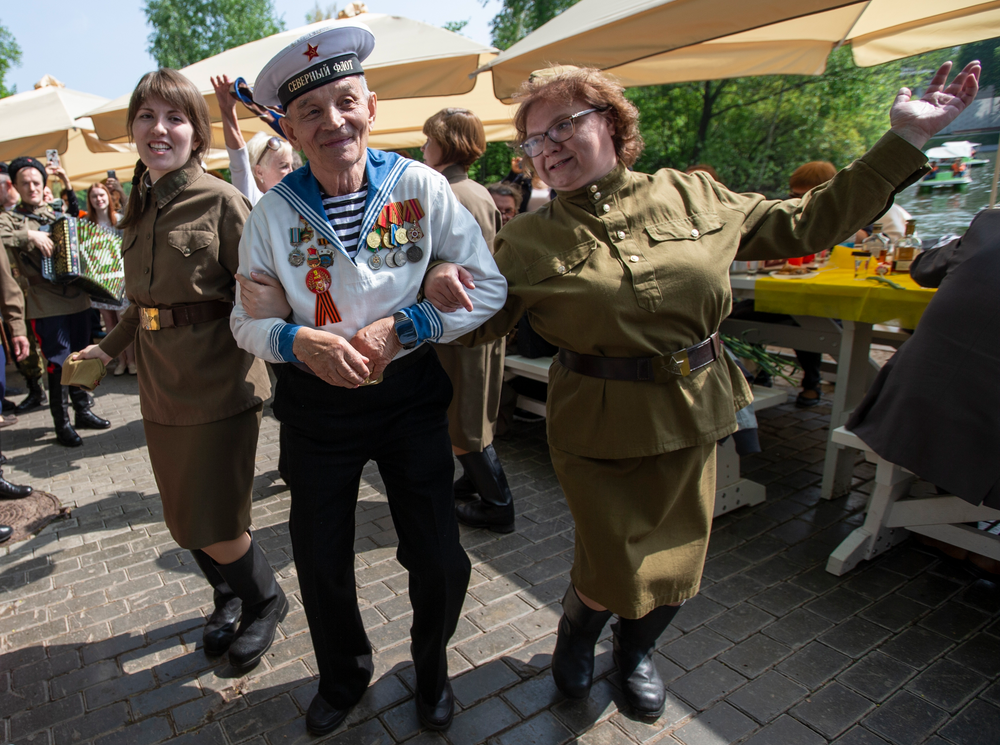Victor Novopashin, 87, a Russian WWII veteran dances with two women dressed in Soviet era uniform celebrate 74 years since the victory in WWII in Gorky Park in Moscow, Russia, Thursday, May 9, 2019. (AP Photo/Alexander Zemlianichenko Jr.)