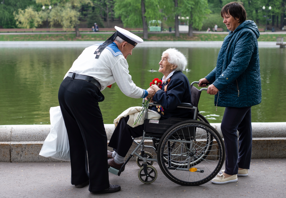 Victor Novopashin, 87, a Russian WWII veteran, left, greets Maria Kanushkina, 95, center, also a Russian WWII veteran celebrating 74 years since the victory in WWII in Gorky Park in Moscow, Russia, Thursday, May 9, 2019. (AP Photo/Alexander Zemlianichenko Jr.)