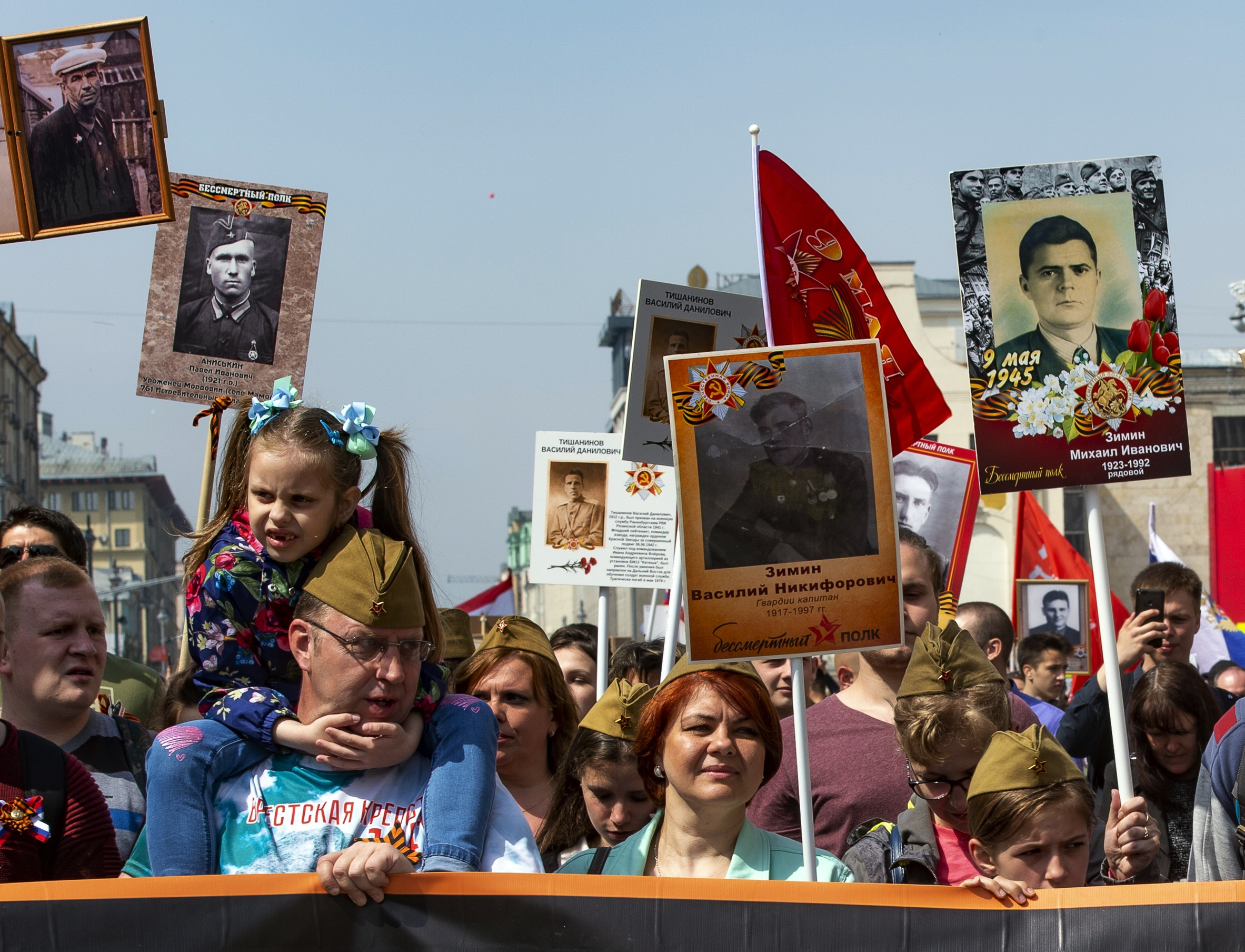 People carry portraits of relatives who fought in World War II, and Soviet flags, during the Immortal Regiment march through the main street toward Red Square in Moscow, Russia, Thursday, May 9, 2019, celebrating 74 years since the end of WWII and the defeat of Nazi Germany. (AP Photo/Dmitry Serebryakov)
