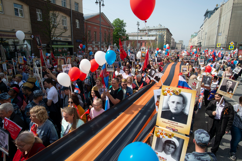 People carry portraits of relatives who fought in World War II, and St. George's ribbon, during the Immortal Regiment march through the main street toward Red Square in Moscow, Russia, Thursday, May 9, 2019, celebrating 74 years since the end of WWII and the defeat of Nazi Germany. (AP Photo/Dmitry Serebryakov)
