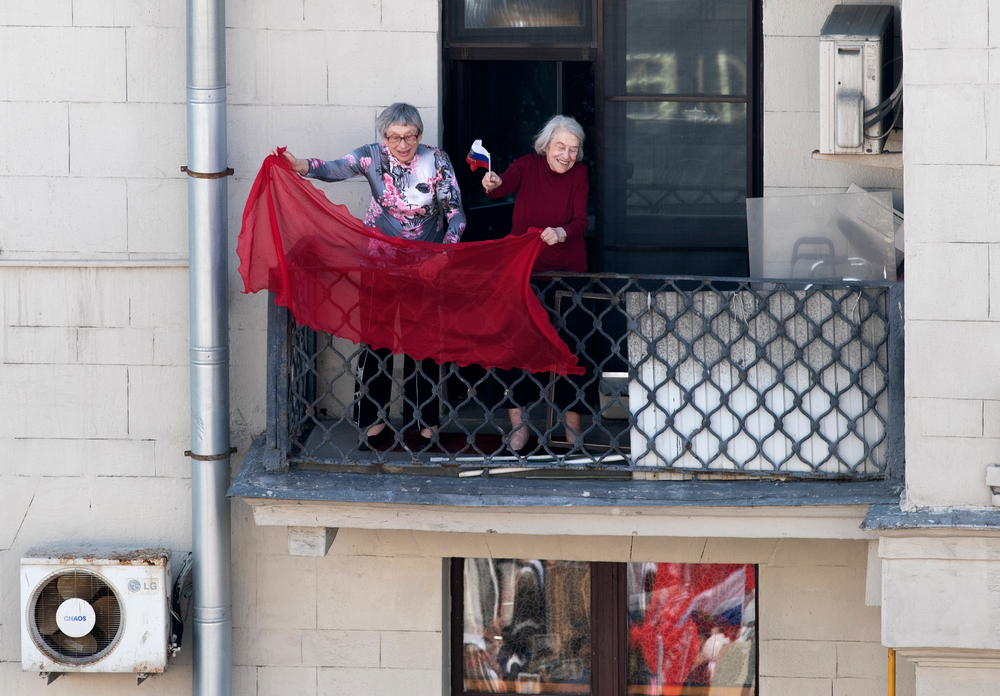 Two elderly women wave a red flag as people carry portraits of relatives who fought in World War II, and Russian and Soviet flags, during the Immortal Regiment march through the main street toward Red Square celebrating 74 years since the victory in WWII in Red Square in Moscow, Russia, Thursday, May 9, 2019. (AP Photo/Denis Tyrin)