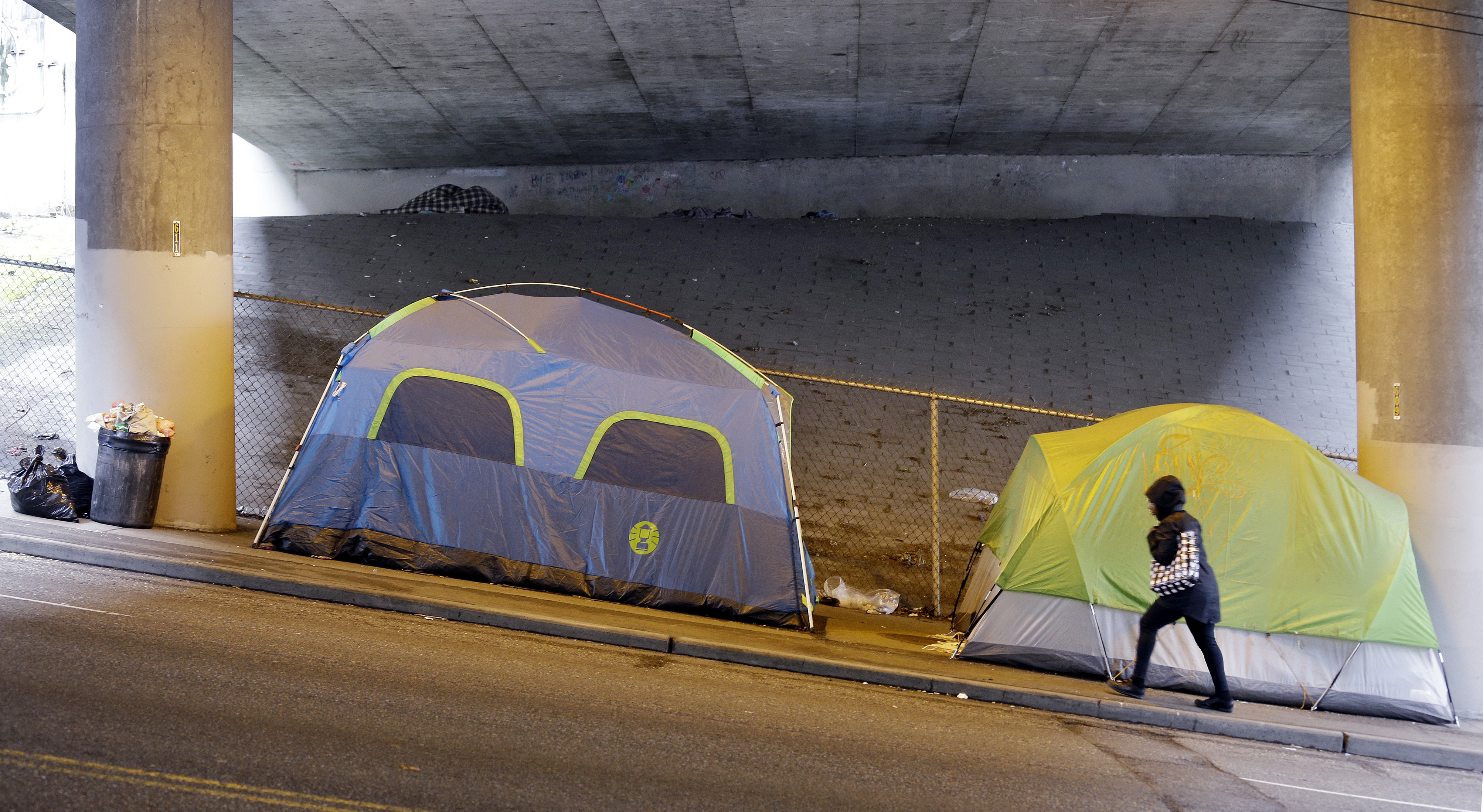 FILE - In this March 8, 2017 file photo, a person walks up a hill next to tents lined up beneath a highway and adjacent to downtown Seattle.   Microsoft pledged $500 million to address homelessness and develop affordable housing in response to the Seattle region's widening affordability gap.  The company plans a news conference, Thursday, Jan. 17, 2019.   (AP Photo/Elaine Thompson, File)