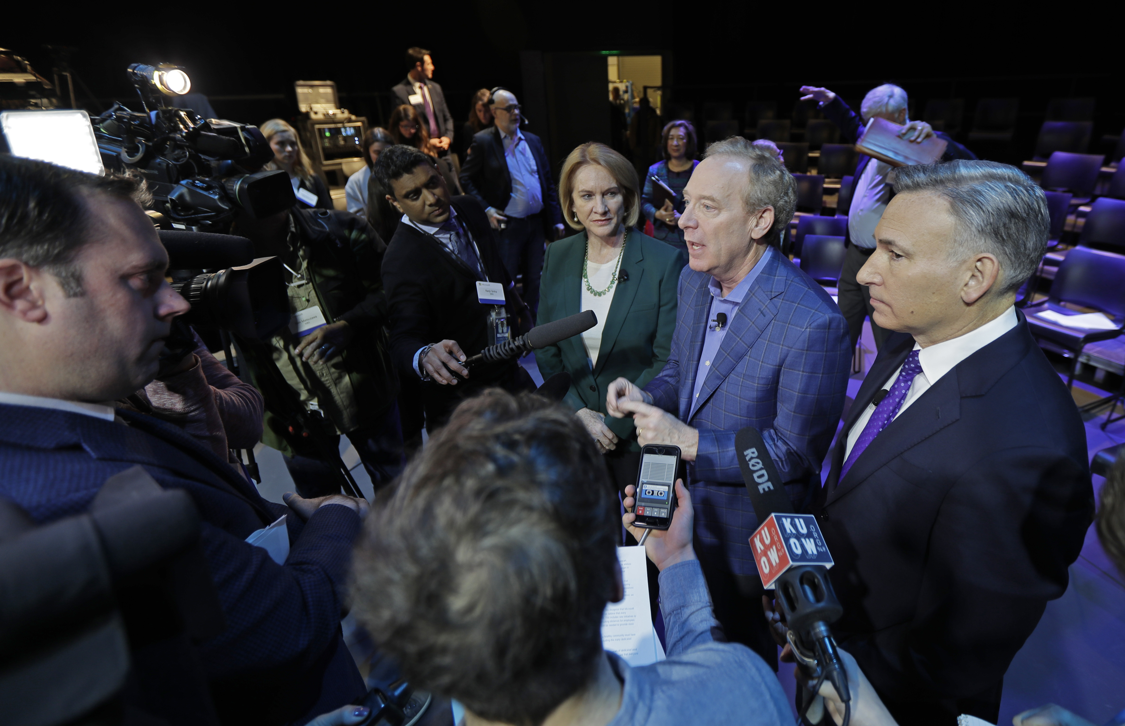 Microsoft Corp. President Brad Smith, second from right, talks to reporters as Seattle Mayor Jenny Durkan, third from right, and King County Executive Dow Constantine, right, look on, Thursday, Jan. 17, 2019, following a news conference in Bellevue, Wash., to announce a $500 million pledge by Microsoft Corp. to develop affordable housing for low- and middle-income workers in response to the Seattle region's widening affordability gap and to also to address homelessness. (AP Photo/Ted S. Warren)