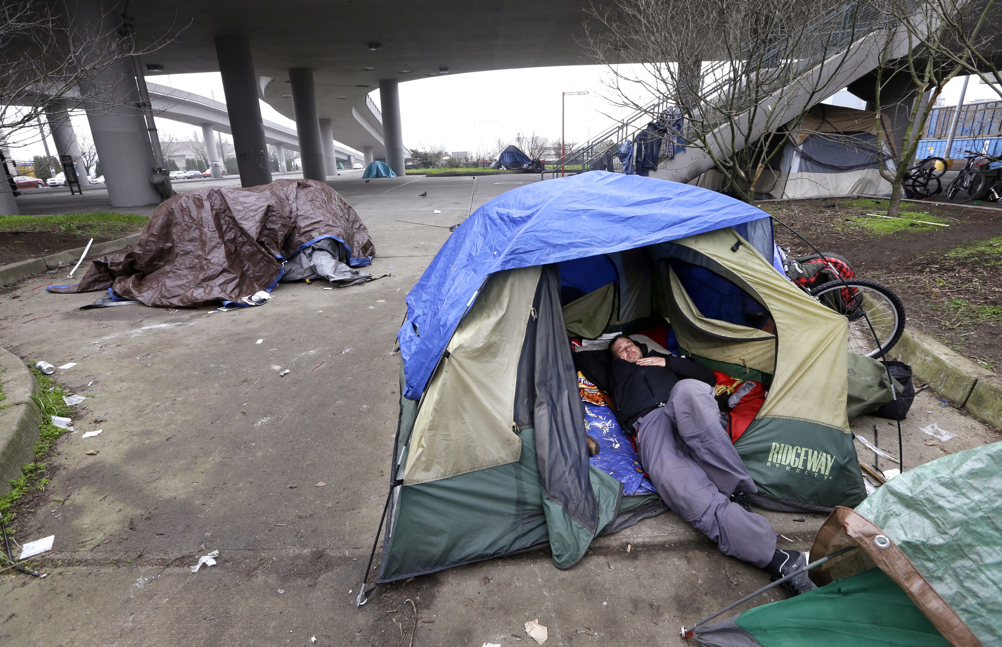 FILE - In this Feb. 9, 2016 file photo, a man lies in a tent with others camped nearby, under and near an overpass in Seattle. Microsoft pledged $500 million to address homelessness and develop affordable housing in response to the Seattle region's widening affordability gap. The company, which plans a news conference Thursday, Jan. 17, 2019, will split the funds three ways. (AP Photo/Elaine Thompson, File)