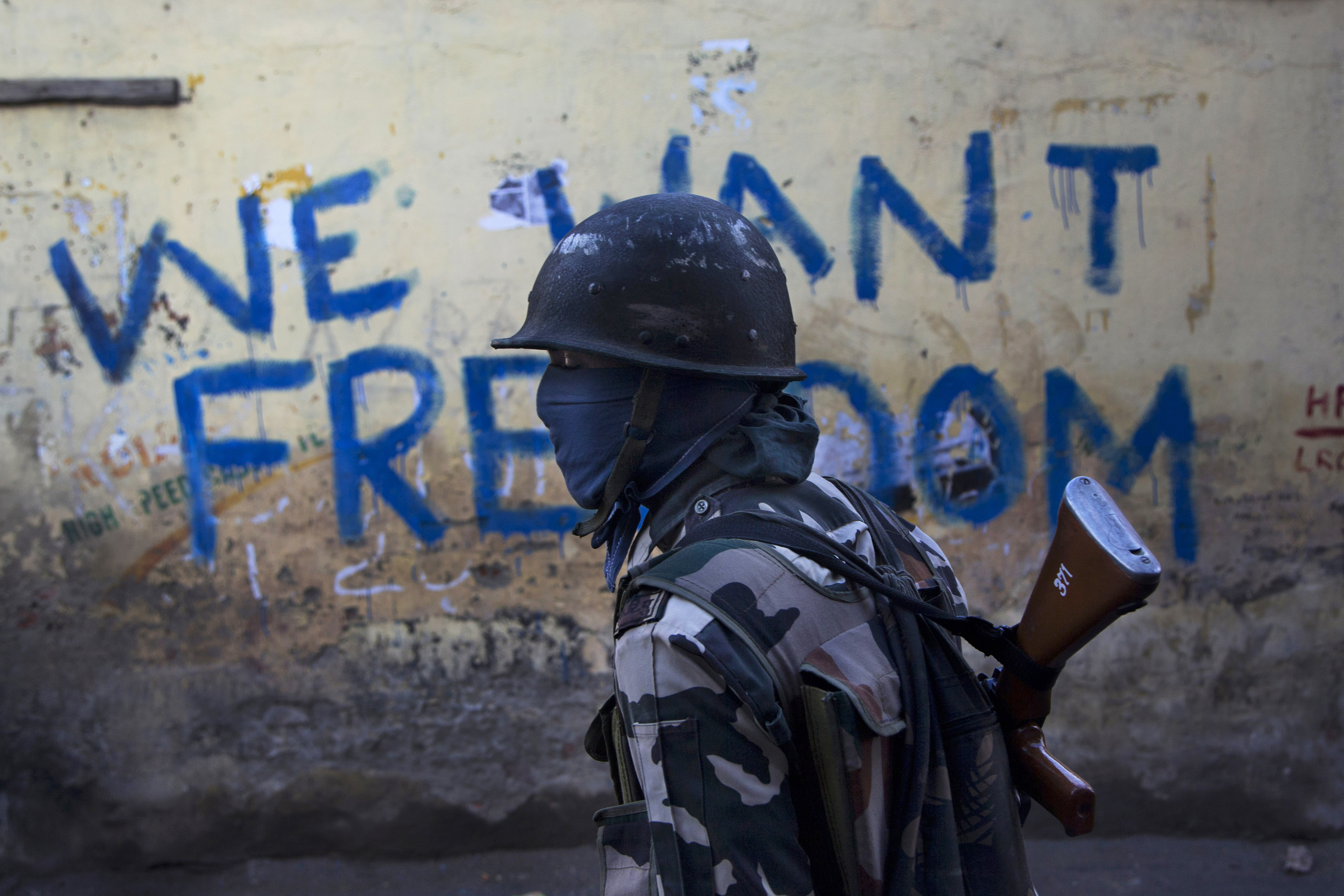 FILE- In this Aug. 29, 2016 file photo, an Indian paramilitary soldier walks past graffiti on a wall in Srinagar, Indian-controlled Kashmir. As India considers its response to the suicide car bombing of a paramilitary convoy in Kashmir that killed dozens of soldiers on Feb. 14, 2019, a retired military commander who oversaw a much-lauded military strike against neighboring Pakistan in 2016 has urged caution. India blamed the attack on Pakistan and promised a