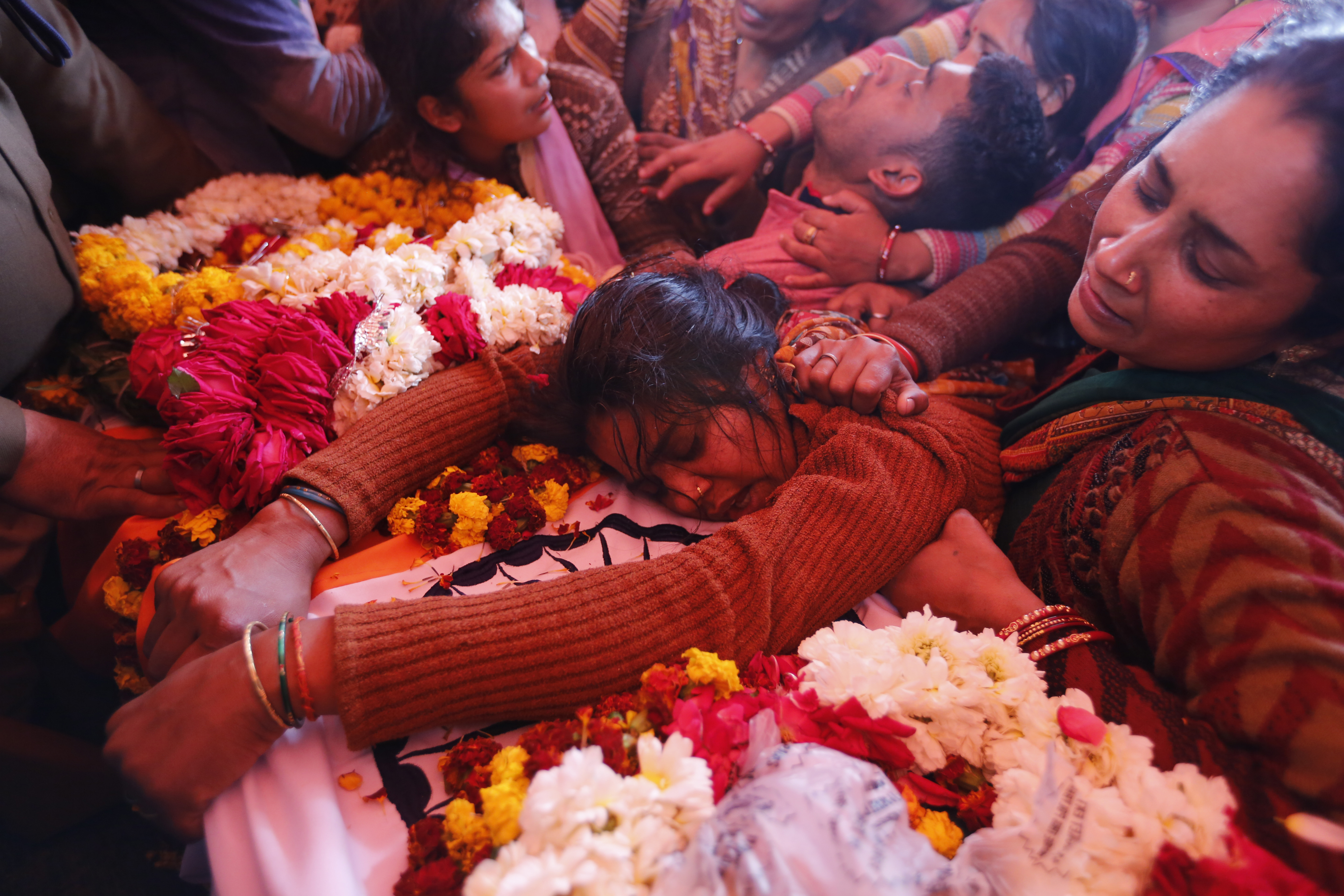 Sanjana cries over the body of her husband Mahesh Yadav, a Central Reserve Police Force (CRPF) soldier who was killed in Thursday bombing in Kashmir, in Tudihar village, some 56 kilometers east of Prayagraj, Uttar Pradesh state, India, Saturday, Feb. 16, 2019. As India considers its response to the suicide car bombing of a paramilitary convoy in Kashmir that killed dozens of soldiers, a retired military commander who oversaw a much-lauded military strike against neighboring Pakistan in 2016 has urged caution. (AP Photo/ Rajesh Kumar Singh)