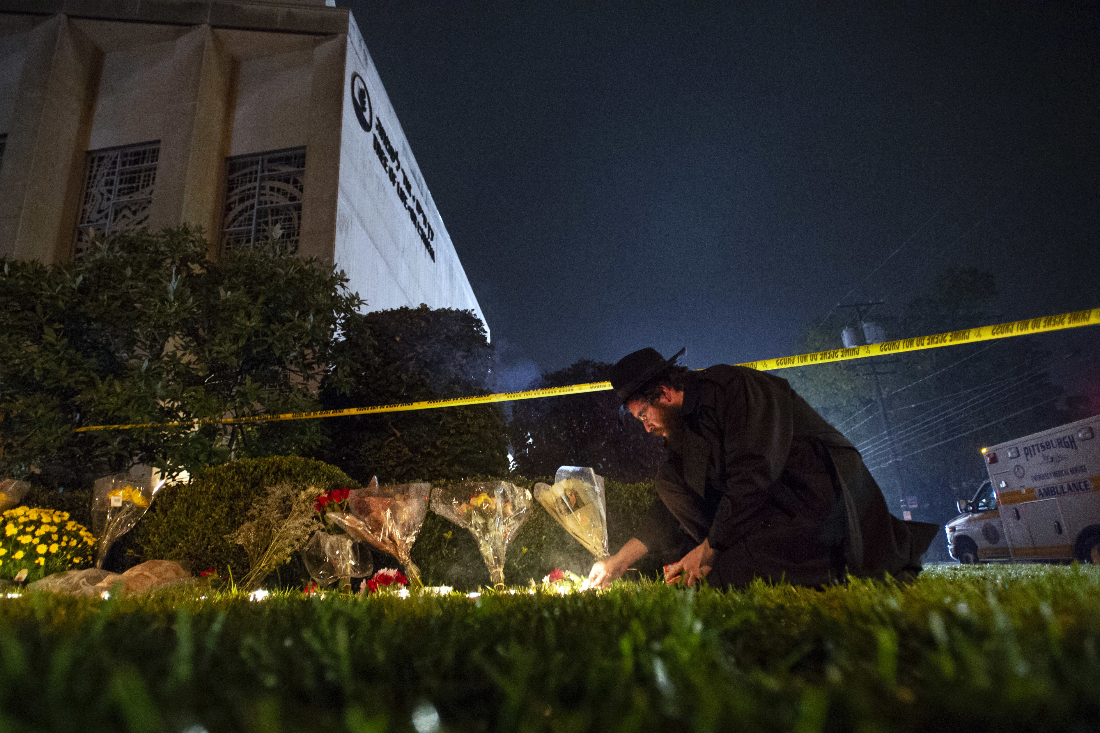 FILE - In this Oct. 27, 2018 photo, Rabbi Eli Wilansky lights a candle after a mass shooting at Tree of Life Synagogue in Pittsburgh's Squirrel Hill neighborhood. Robert Bowers, a truck driver accused of killing 11 and wounding seven during an attack on the Pittsburgh synagogue in October is expected to appear Monday, Feb. 11, 2019, morning in a federal courtroom to be arraigned on additional charges. (Steph Chamber/Pittsburgh Post-Gazette via AP, File)
