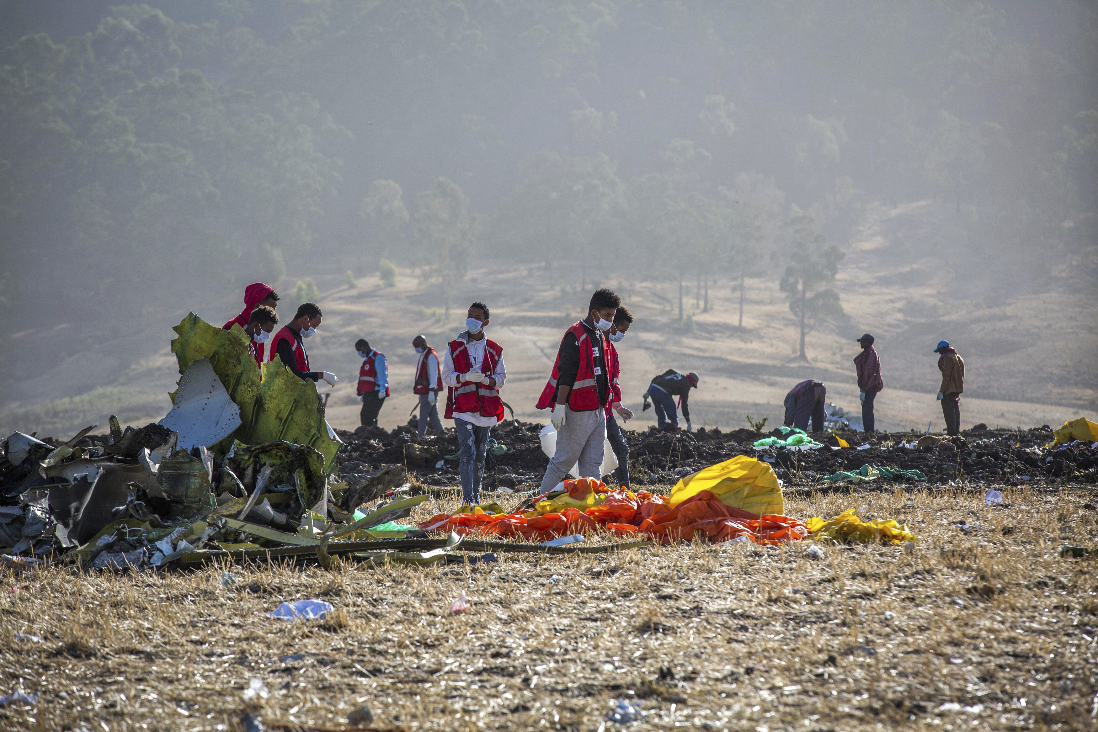 FILE- In this March 11, 2019, file photo rescuers work at the scene of an Ethiopian Airlines flight crash near Bishoftu, or Debre Zeit, south of Addis Ababa, Ethiopia. Investigators have determined that an anti-stall system automatically activated before the Ethiopian Airlines Boeing 737 Max jet plunged into the ground, The Wall Street Journal reported Friday, March 29. (AP Photo/Mulugeta Ayene, File)