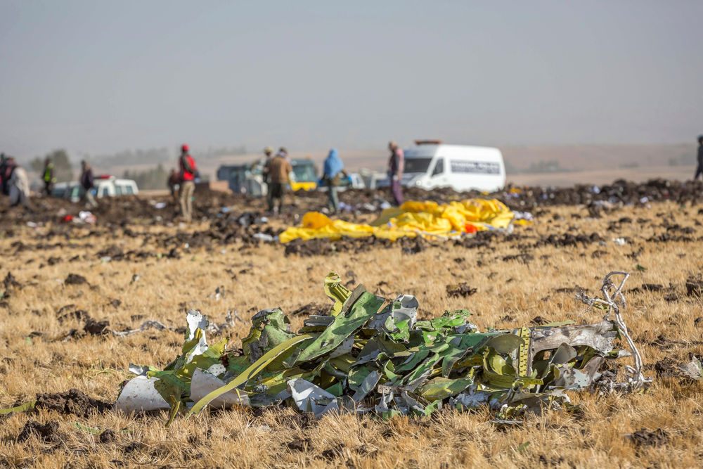 FILE- In this March 11, 2019, file photo parts of the plane wreckage with rescue workers at the crash site at Bishoftu, or Debre Zeit, outside Addis Ababa, Ethiopia. Investigators have determined that an anti-stall system automatically activated before the Ethiopian Airlines Boeing 737 Max jet plunged into the ground, The Wall Street Journal reported Friday, March 29. (AP Photo/Mulugeta Ayene, File)