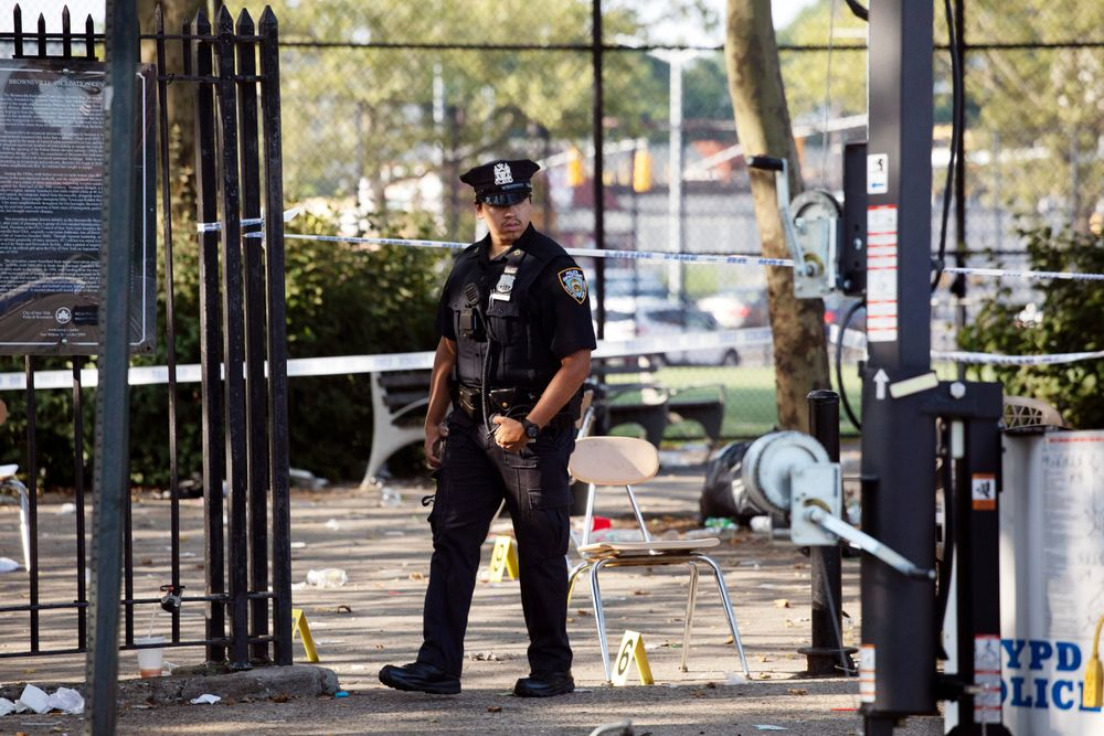 A police officer walks by yellow evidence markers at a playground in the Brownsville neighborhood in the Brooklyn borough of New York, Sunday, July 28, 2019. Police said, one man was killed and at least 11 others were injured in a shooting late Saturday night at the park. (AP Photo/Mark Lennihan)