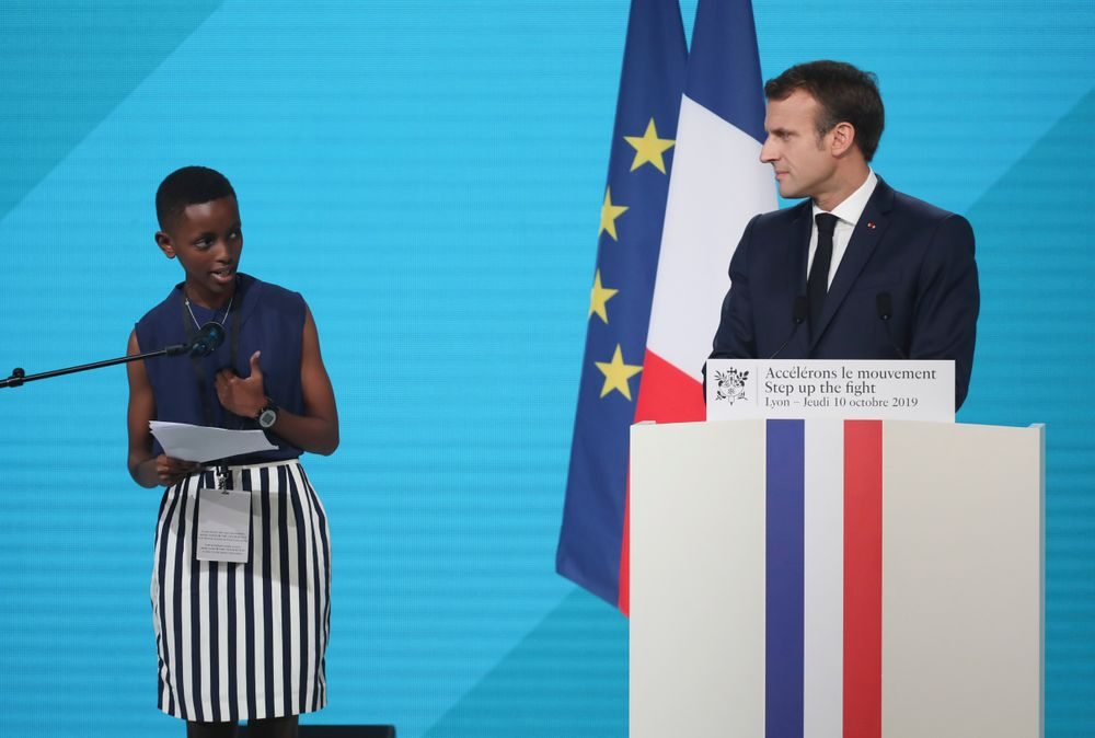 France's President Emmanuel Macron, right, listening to the goodwill ambassador of the ONG