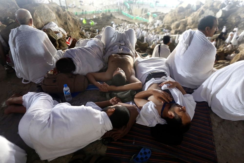 Muslim pilgrims take a nap on a rocky hill known as Mountain of Mercy, on the Plain of Arafat, during the annual hajj pilgrimage, ahead of sunrise near the holy city of Mecca, Saudi Arabia, Saturday, Aug. 10, 2019. More than 2 million pilgrims were gathered to perform initial rites of the hajj, an Islamic pilgrimage that takes the faithful along a path traversed by the Prophet Muhammad some 1,400 years ago. (AP Photo/Amr Nabil)