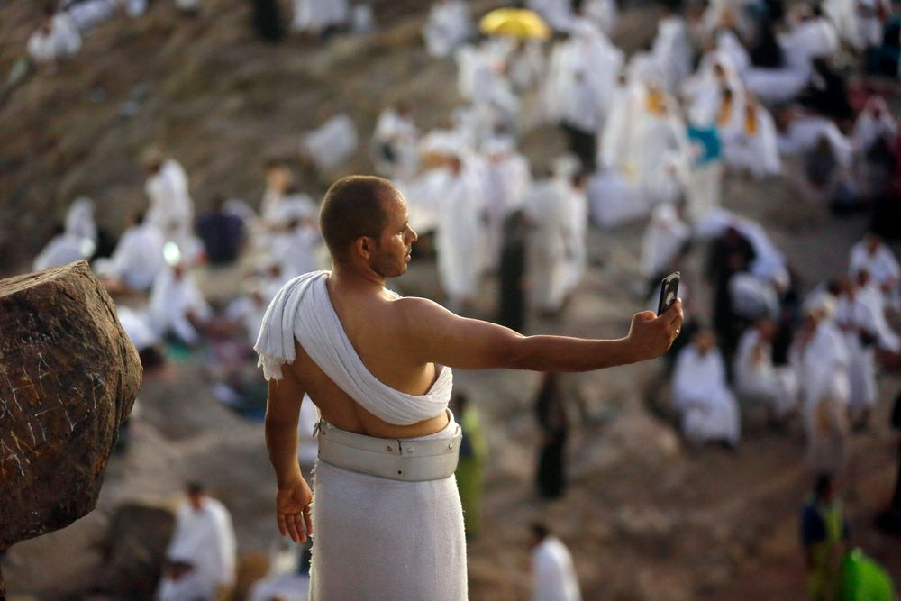 A Muslim pilgrim takes a selfie on a rocky hill known as Mountain of Mercy, on the Plain of Arafat, during the annual hajj pilgrimage, near the holy city of Mecca, Saudi Arabia, Saturday, Aug. 10, 2019. More than 2 million pilgrims were gathered to perform initial rites of the hajj, an Islamic pilgrimage that takes the faithful along a path traversed by the Prophet Muhammad some 1,400 years ago. (AP Photo/Amr Nabil)