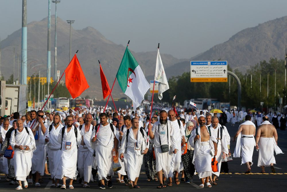 Algerian pilgrims march towards the Mountain of Mercy, on the Plain of Arafat, during the annual hajj pilgrimage, near the holy city of Mecca, Saudi Arabia, Saturday, Aug. 10, 2019. More than 2 million pilgrims were gathered to perform initial rites of the hajj, an Islamic pilgrimage that takes the faithful along a path traversed by the Prophet Muhammad some 1,400 years ago. (AP Photo/Amr Nabil)