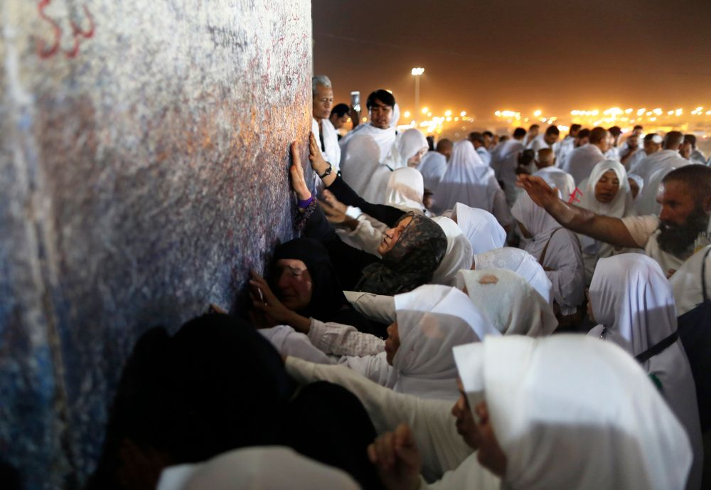 Muslim pilgrims pray in front of a pillar, where Islam's Prophet Muhammad is believed to have delivered his last sermon to tens of thousands of followers, on a rocky hill known as Mountain of Mercy, on the Plain of Arafat, during the annual hajj pilgrimage, ahead of sunrise near the holy city of Mecca, Saudi Arabia, Saturday, Aug. 10, 2019. More than 2 million pilgrims were gathered to perform initial rites of the hajj, an Islamic pilgrimage that takes the faithful along a path traversed by the Prophet Muhammad some 1,400 years ago. (AP Photo/Amr Nabil)