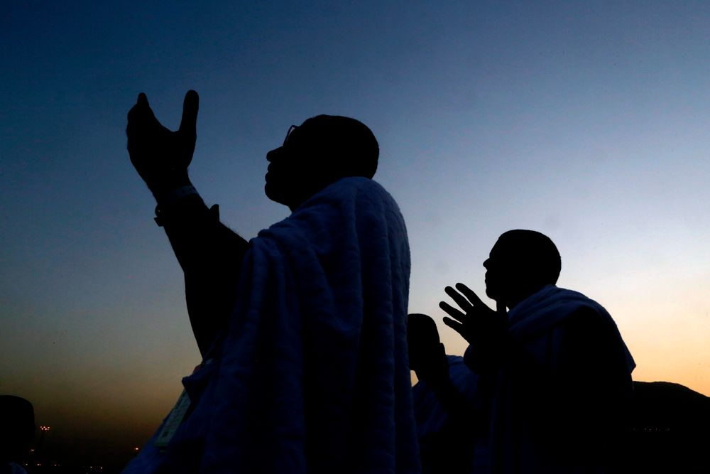 Muslim pilgrims pray on a rocky hill known as Mountain of Mercy, on the Plain of Arafat, during the annual hajj pilgrimage ahead of sunrise near the holy city of Mecca, Saudi Arabia, Saturday, Aug. 10, 2019. More than 2 million pilgrims were gathered to perform initial rites of the hajj, an Islamic pilgrimage that takes the faithful along a path traversed by the Prophet Muhammad some 1,400 years ago. (AP Photo/Amr Nabil)