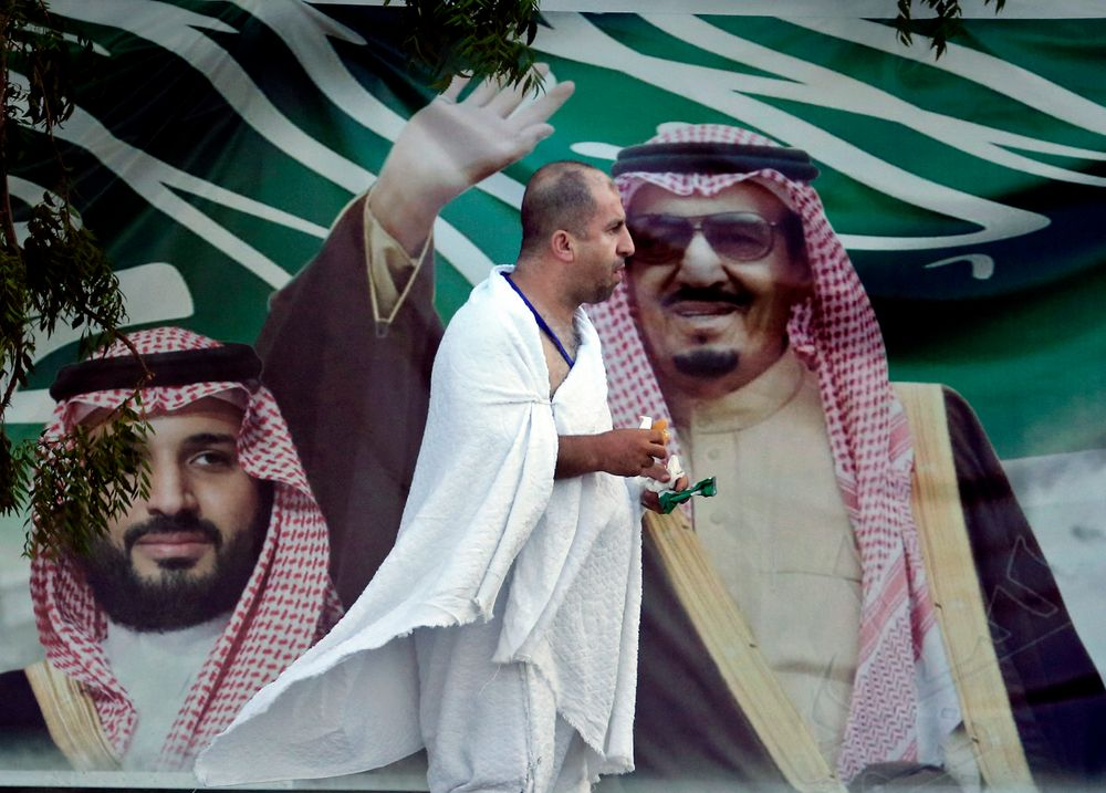 A Lebanese pilgrim walks in front of a banner showing Saudi King Salman, right, and his Crown Prince Mohammed bin Salman, near the Mountain of Mercy, on the Plain of Arafat, during the annual hajj pilgrimage, near the holy city of Mecca, Saudi Arabia, Saturday, Aug. 10, 2019. More than 2 million pilgrims were gathered to perform initial rites of the hajj, an Islamic pilgrimage that takes the faithful along a path traversed by the Prophet Muhammad some 1,400 years ago. (AP Photo/Amr Nabil)