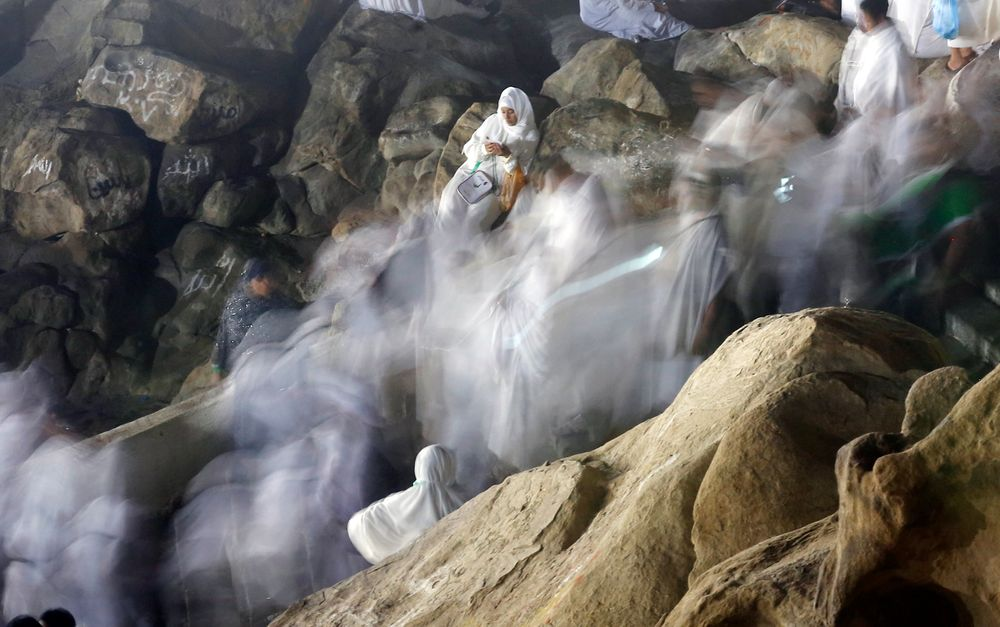 In this picture taken with low shutter speed, Muslim pilgrims make their way up on a rocky hill known as Mountain of Mercy, on the Plain of Arafat, during the annual hajj pilgrimage, ahead of sunrise near the holy city of Mecca, Saudi Arabia, Saturday, Aug. 10, 2019. More than 2 million pilgrims were gathered to perform initial rites of the hajj, an Islamic pilgrimage that takes the faithful along a path traversed by the Prophet Muhammad some 1,400 years ago. (AP Photo/Amr Nabil)