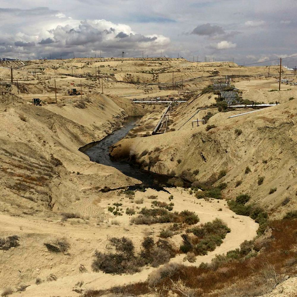 In this May 10, 2019 photo provided by the California Department of Fish and Wildlife's Office of Spill Prevention and Response, oil flows at a Chevron oil field in Kern County, Calif. Nearly 800,000 gallons of oil and water has seeped from the ground since May. Chevron and California officials say the spill is not near any waterway and has not significantly affected wildlife. (California Deptartment of Fish and Wildlife's Office of Spill Prevention and Response via AP)