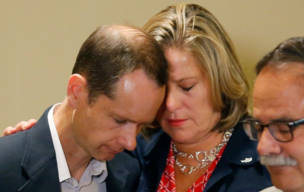 FILE - In this June 27, 2019, file photo, Matthew and Jill McCluskey, parents of Lauren McCluskey, hug after speaking during a news conference in Salt Lake City. The parents of Lauren, a University of Utah student and track athlete who was fatally shot on campus, are fighting a claim by the college that their lawsuit should be dismissed because their daughter's killer wasn't a student. Campus police could have contacted the killer's parole officer or kept him off campus after Lauren and her friends reported his harassment and an extortion attempt, lawyers for Jill and Matthew McCluskey argued in a court filing Monday, Nov. 25. (AP Photo/Rick Bowmer, File)