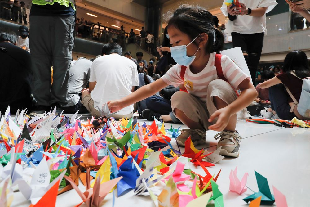 A child arranges origami cranes used in an anti-government rally inside a shopping mall at the Sha Tin district in Hong Kong, Sunday, Sept. 22, 2019. Young protesters, many wearing masks to disguise their identity, filled the open area of a Hong Kong shopping mall Sunday and folded paper