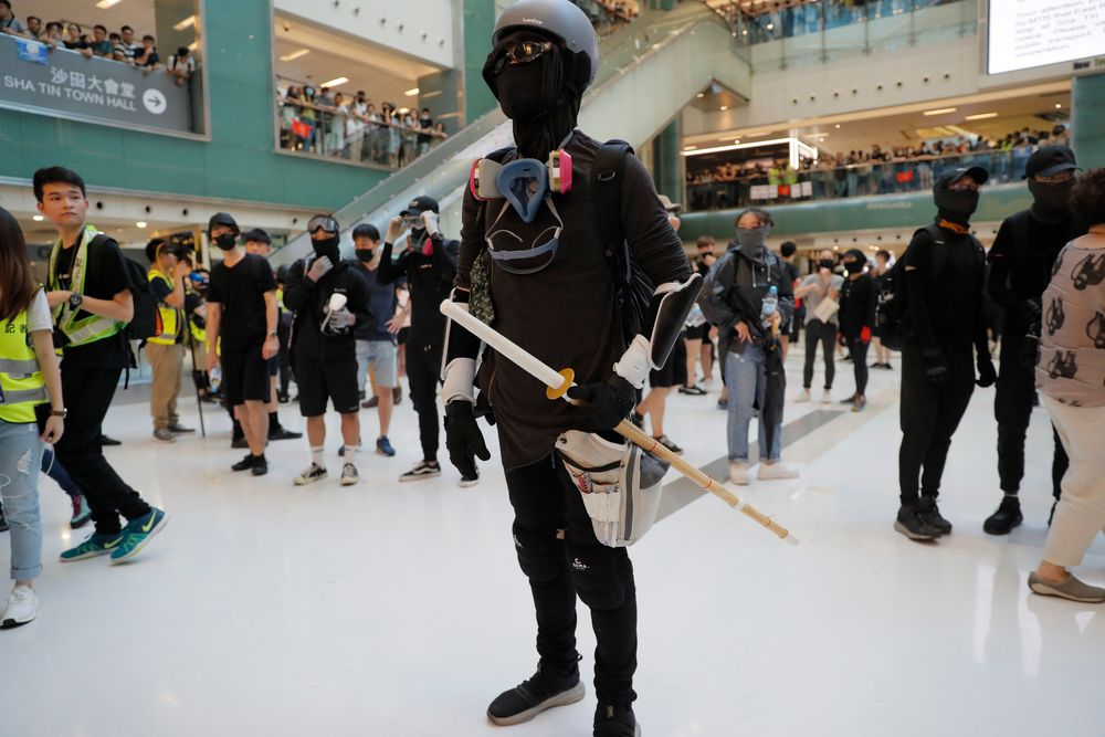 A protester armed with a wooden weapon stands in a mall during a protest in Hong Kong on Sunday, Sept. 22, 2019. Protesters smashed surveillance cameras and electronic ticket sensors in a subway station, as pro-democracy demonstrations took a violent turn once again. (AP Photo/Kin Cheung)