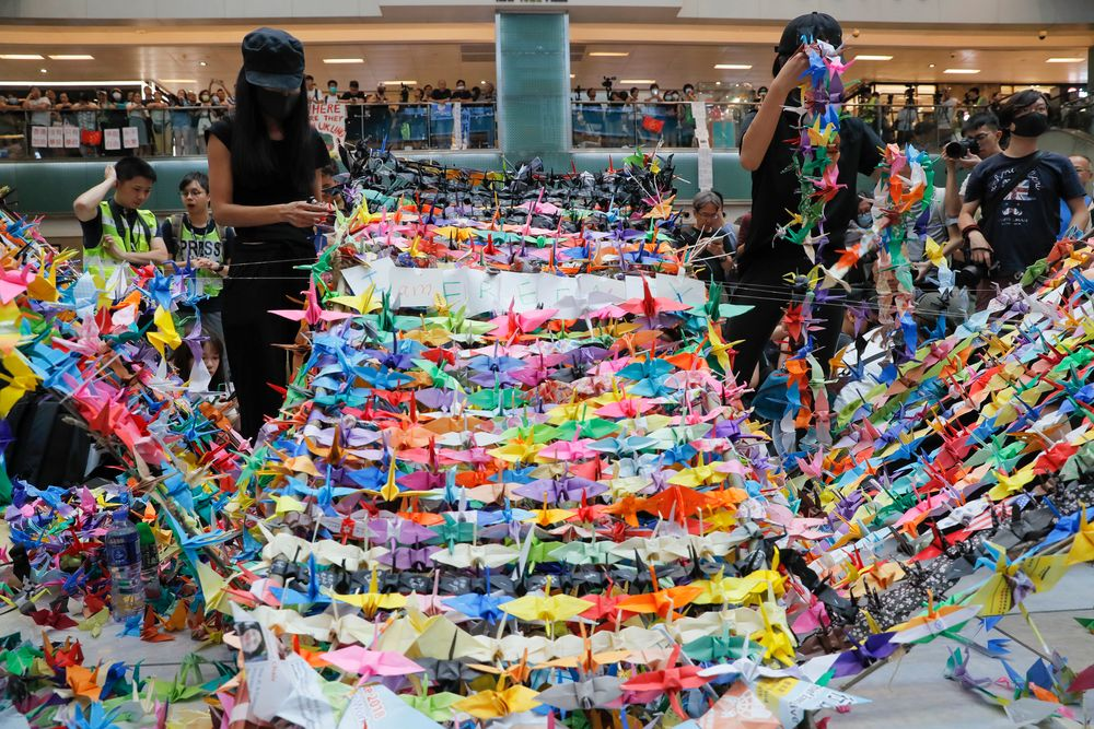 Protesters arranging origami cranes used in a display at an anti-government rally inside a shopping mall at the Sha Tin district, Sunday, Sept. 22, 2019. Protesters in Hong Kong burned a Chinese flag and police fired pepper spray Saturday in renewed clashes over grievances by the anti-government demonstrators. (AP Photo/Vincent Yu)