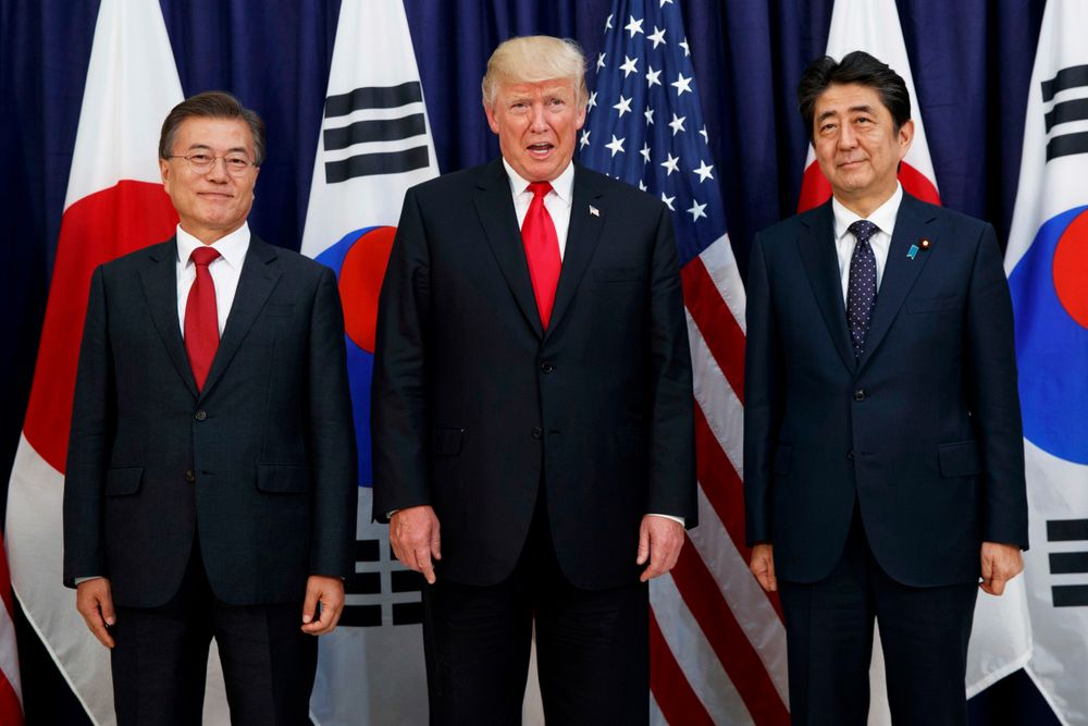 FILE - In this July 6, 2017, file photo, U.S. President Donald Trump, center, meets with Japanese Prime Minister Shinzo Abe, right, and South Korean President Moon Jae-in before the Northeast Asia Security dinner at the U.S. Consulate General Hamburg in Germany. In August 2019, Trump angered some Asian American voters after the New York Post reported that he mocked the accents of Moon and Abe at a fundraiser in the Hamptons. (AP Photo/Evan Vucci, File)