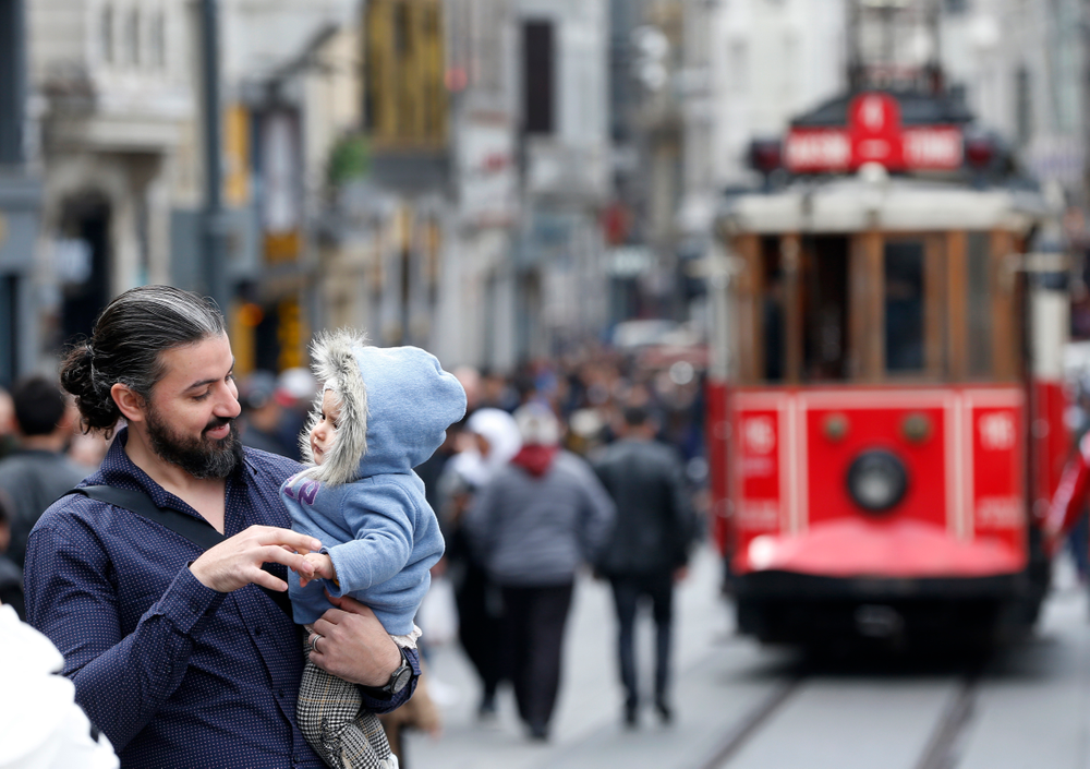 In this Thursday, April 4, 2019 photo, a man holds his baby, in Istiklal street, the main shopping street in Istanbul. The mood among opposition supporters in Turkey's biggest city is one of jubilation but also worry - fear that their win in Istanbul's mayoral race could be overturned in a recount taking place after the ruling party challenged the election results. (AP Photo/Lefteris Pitarakis)